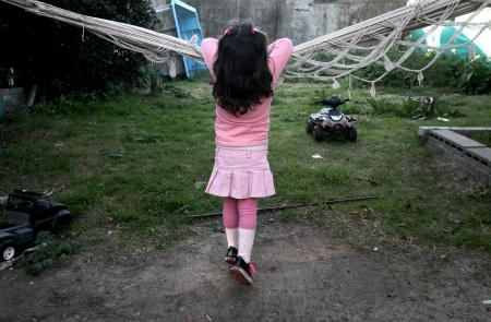 Lulu, a transgender girl, leans on a hammock at her home in Buenos Aires July 25, 2013. Lulu, a six-year-old Argentine child who was listed as a boy at birth, has been granted new identification papers by the Buenos Aires provincial government listing her as a girl. According to her mother Gabriela, Lulu chose the gender as soon as she first learned to speak. Gabriela said her child, named Manuel at birth, insisted on being called Lulu since she was just four years old, local media reported. Argentina in 2012 put in place liberal rules on changing gender, allowing people to alter their gender on official documents without first having to receive a psychiatric diagnosis or surgery. Picture taken on July 25, 2013. REUTERS/Stringer (ARGENTINA - Tags: SOCIETY HEALTH) - RTX141CN