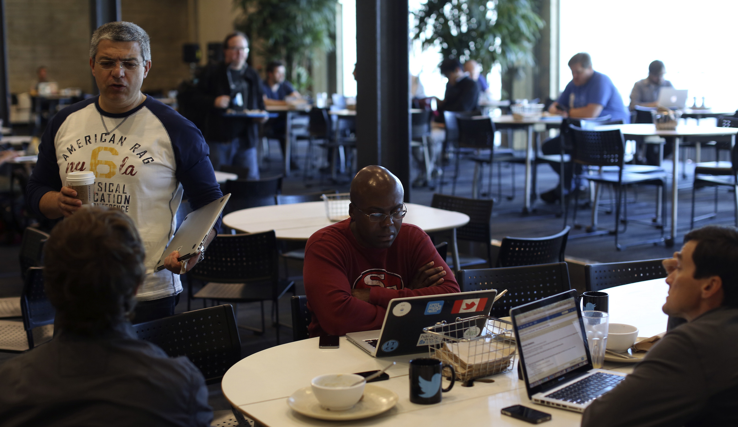 Employees talk in the dining area at Twitter's headquarters in San Francisco, California October 4, 2013. Twitter Inc is likely to price its hotly anticipated initial public offering later on November 6, 2013 above an already bumped-up target range, sources familiar with the process said. Picture taken October 4. REUTERS/Robert Galbraith  (UNITED STATES - Tags: SCIENCE TECHNOLOGY BUSINESS EMPLOYMENT) - RTX152SL