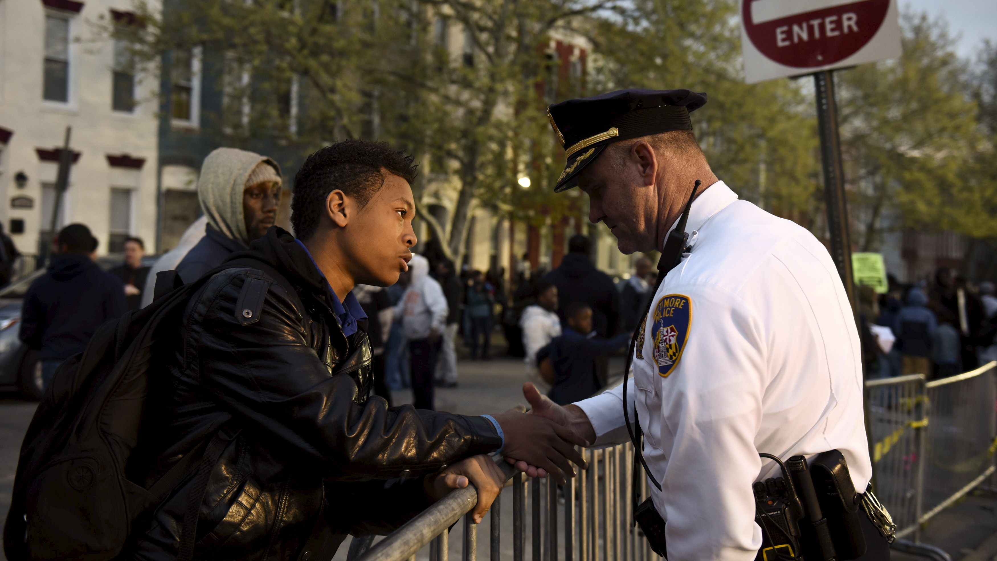 Ninth-grader Tremaine Holmes shakes hands with Captain Erik Pecha in front of the Baltimore Police Department.