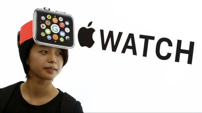 A woman wearing a mock-up of an Apple Watch stands in front of an Apple sign at an electronics store in Tokyo April 24, 2015.