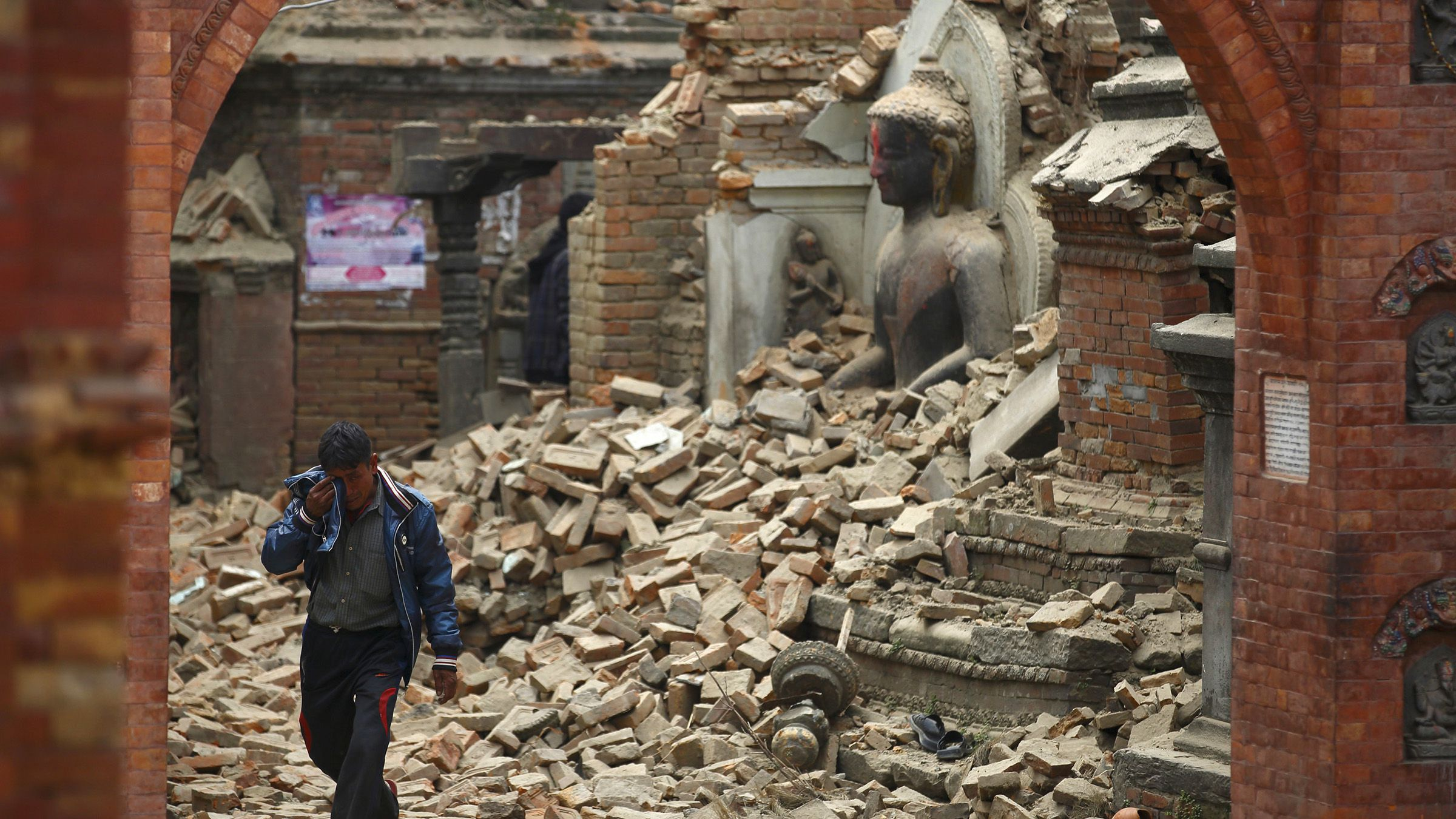 A man cries as he walks on the street while passing through a damaged statue of Lord Buddha a day after an earthquake in Bhaktapur, Nepal April 26, 2015. Rescuers dug with their bare hands and bodies piled up in Nepal on Sunday after the earthquake devastated the heavily crowded Kathmandu valley, killing at least 1,900, and triggered a deadly avalanche on Mount Everest.  REUTERS/Navesh Chitrakar      TPX IMAGES OF THE DAY      - RTX1AAS7