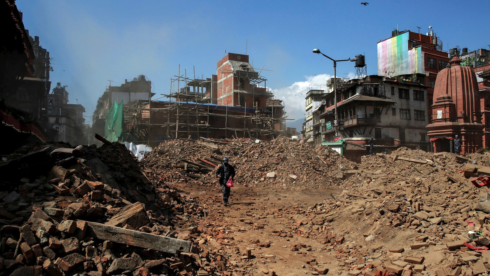 A member of Nepalese police personnel walks amidst the rubble of collapsed buildings, in the aftermath of Saturday's earthquake in Kathmandu, Nepal, April 27, 2015.