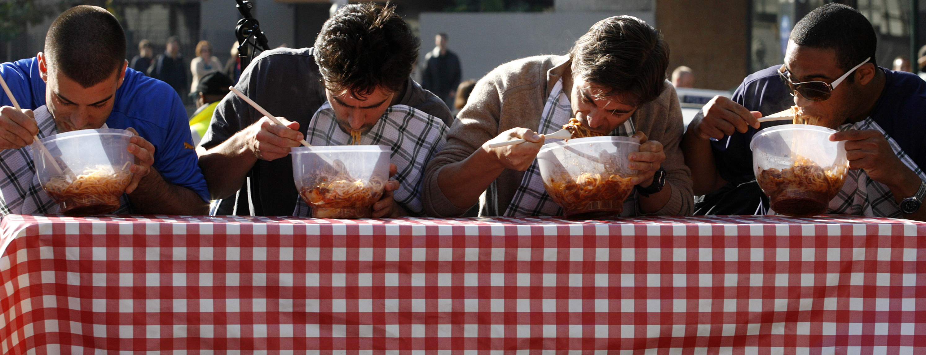 People participate in a spaghetti eating competition at the Sydney Italian Festival May 25, 2008. The festival, which coincides with celebrations for Italian National Day on June 2, runs till June 10.   REUTERS/Daniel Munoz   (AUSTRALIA) - RTX651W