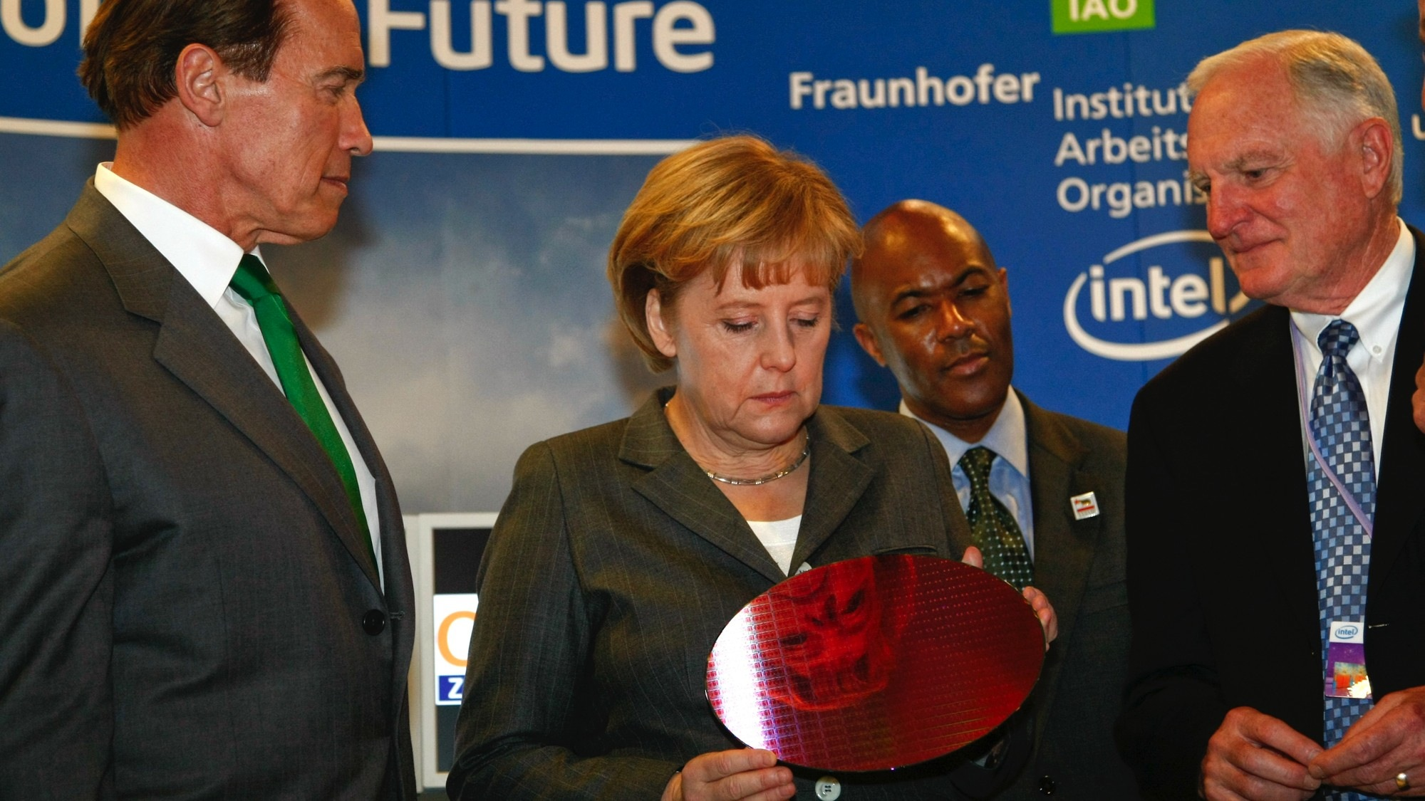 California Governor Arnold Schwarzenegger (L) and Craig R. Barrett, CEO of Intel (R) look to German Chancellor Angela Merkel (C) as she holds a chip wafer at the booth of Intel during the opening tour of the CeBIT computer fair in Hanover March 3, 2009. The world's biggest IT fair CeBIT with 4300 exhibitors from 69 countries opens its doors to the public on March 3, and runs through March 8, 2009.  REUTERS/Fabrizio Bensch (GERMANY) - RTXCAI1