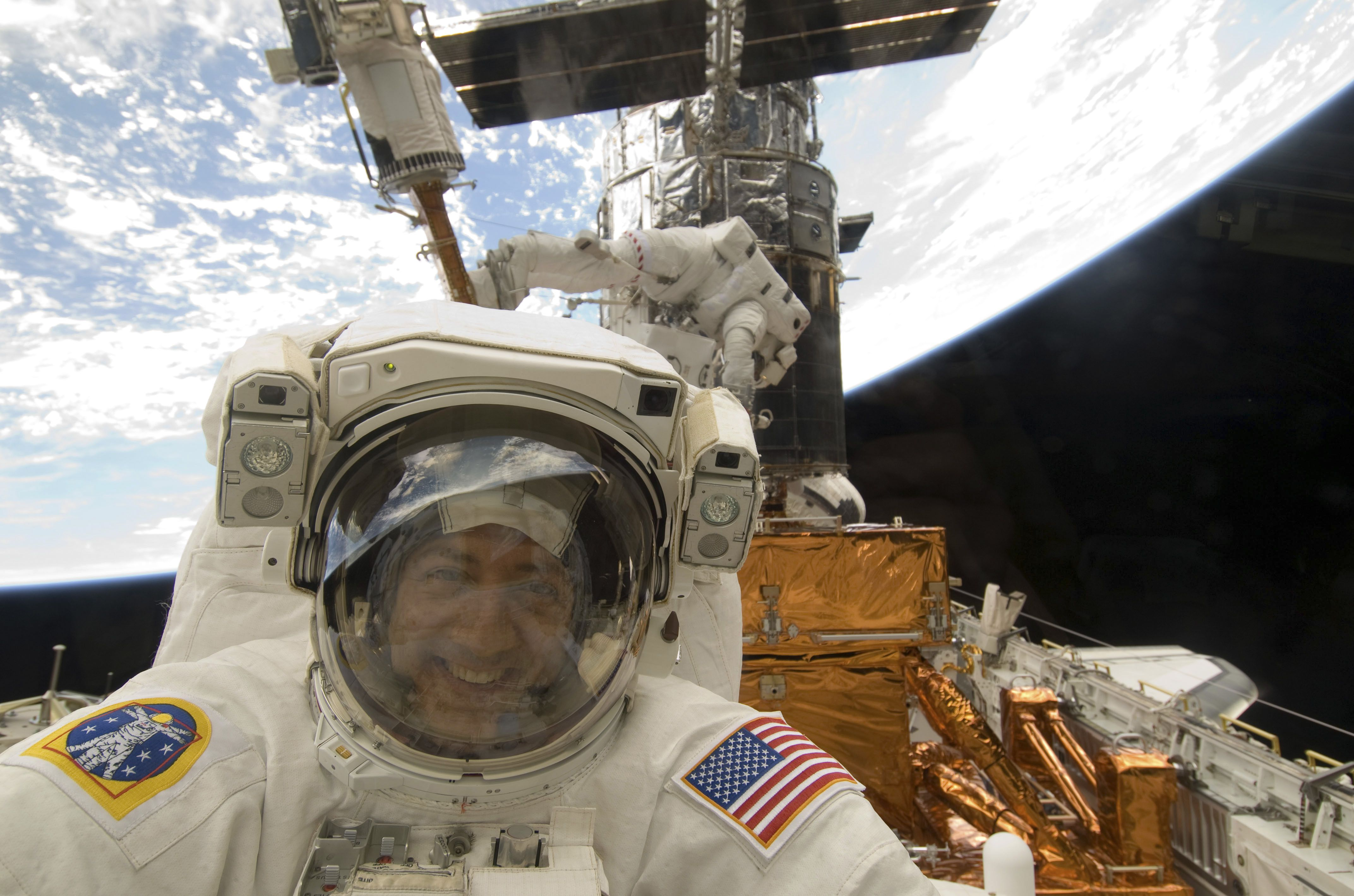 NASA astronaut Mike Massimino, STS-125 mission specialist, is pictured as he peers through a window on the aft flight deck of the Earth-orbiting Space Shuttle Atlantis during the mission's fourth spacewalk to refurbish and upgrade the Hubble Space Telescope on May 17, 2009. During the eight-hour, two-minute spacewalk, Massimino and astronaut Michael Good (background), mission specialist, continued repairs and improvements to the Space Telescope Imaging Spectrograph (STIS) that will extend the Hubble's life into the next decade.  REUTERS/NASA/Handout  (UNITED STATES ENVIRONMENT SCI TECH) FOR EDITORIAL USE ONLY. NOT FOR SALE FOR MARKETING OR ADVERTISING CAMPAIGNS - RTXJJ1C
