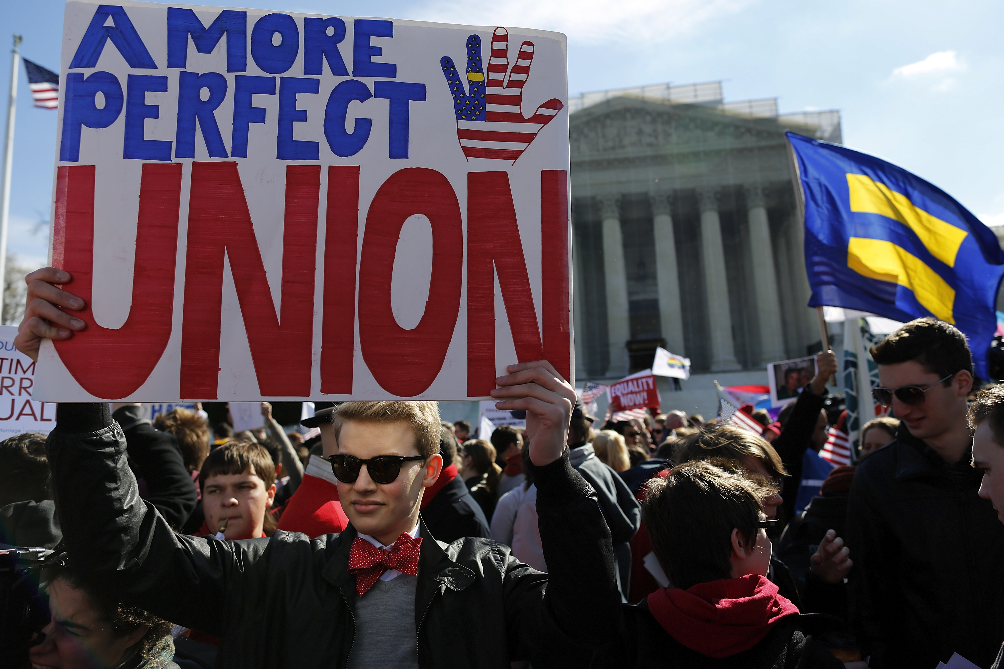 Protestors hold signs and flags as they rally against the Defense of Marriage Act in front of the U.S. Supreme Court in Washington