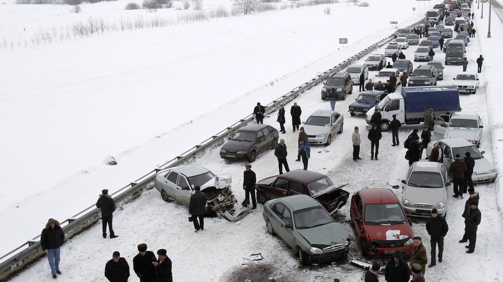 People stand at the site of a car accident which caused a traffic jam on a road from the airport to the city of Kazan, some 800 kms (496 miles) east of Moscow, March 11, 2010.