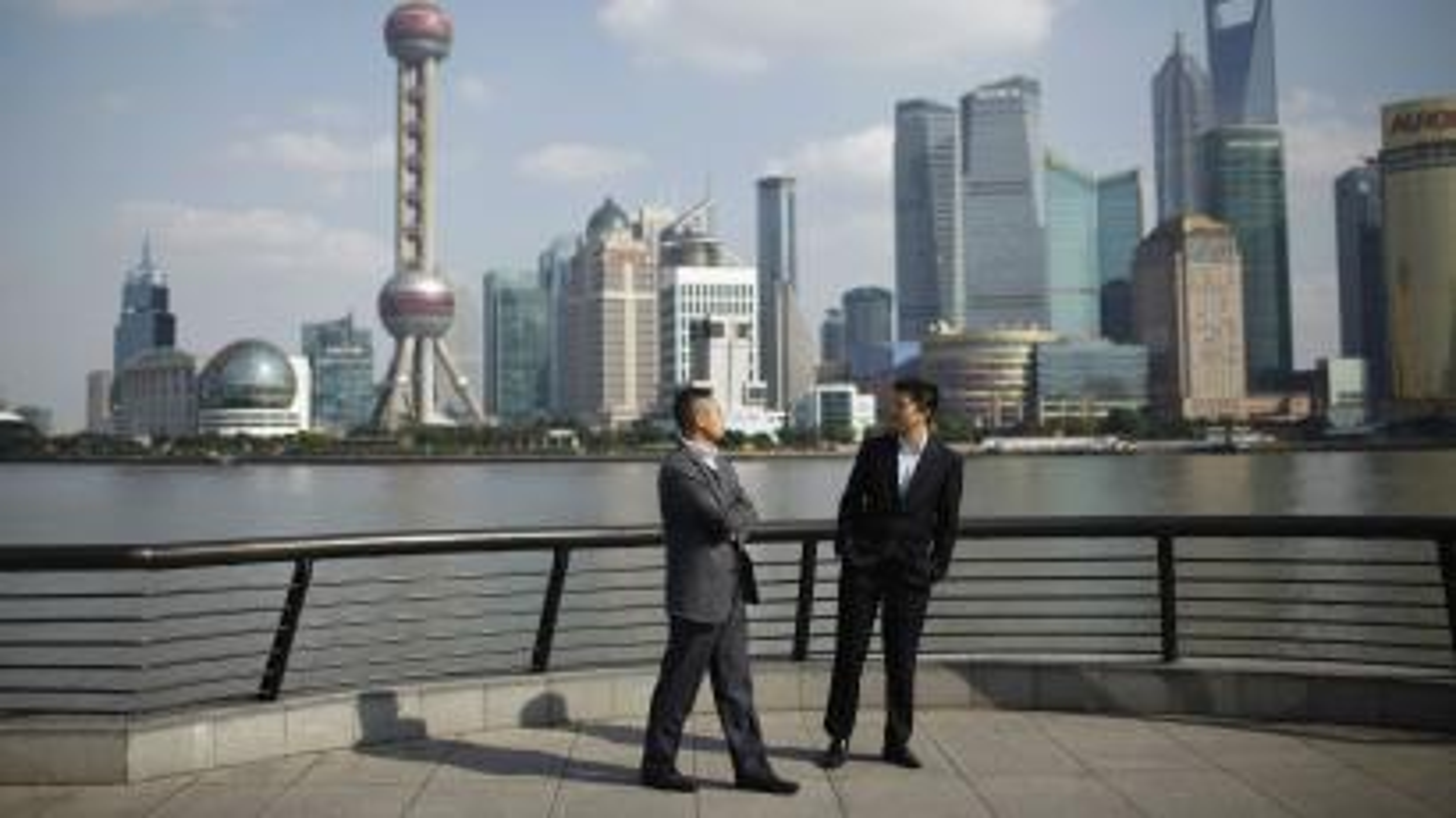 Businessmen walk on the Bund near Shanghai's financial district.
