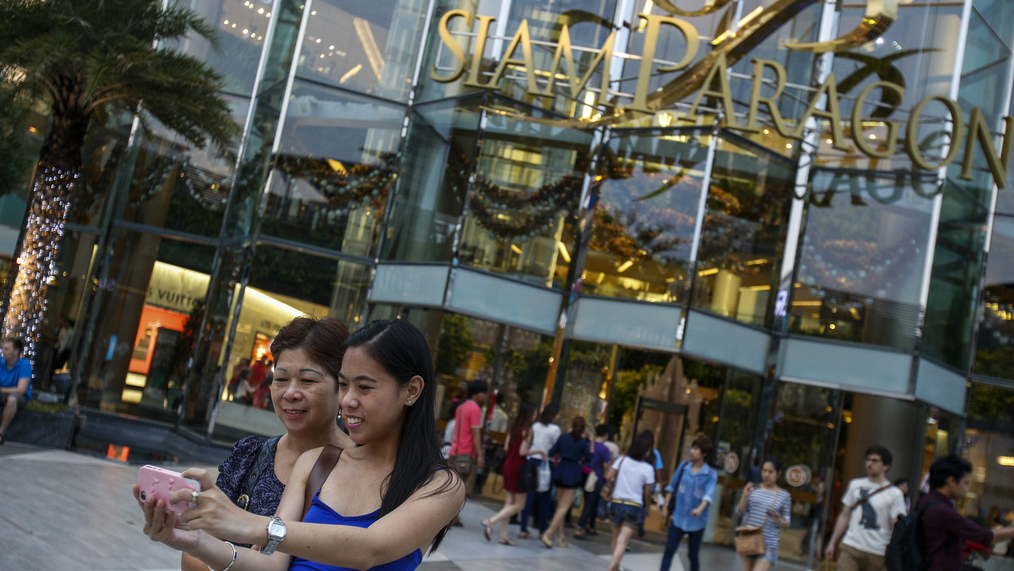 Tourists take a photo of themselves in front of Siam Paragon Department Store in central Bangkok December 16, 2013. Bangkok's Siam Paragon shopping mall is the most popular location among Instagram users, and Bangkok the second most popular city this year, the network's blog announced. REUTERS/Athit Perawongmetha