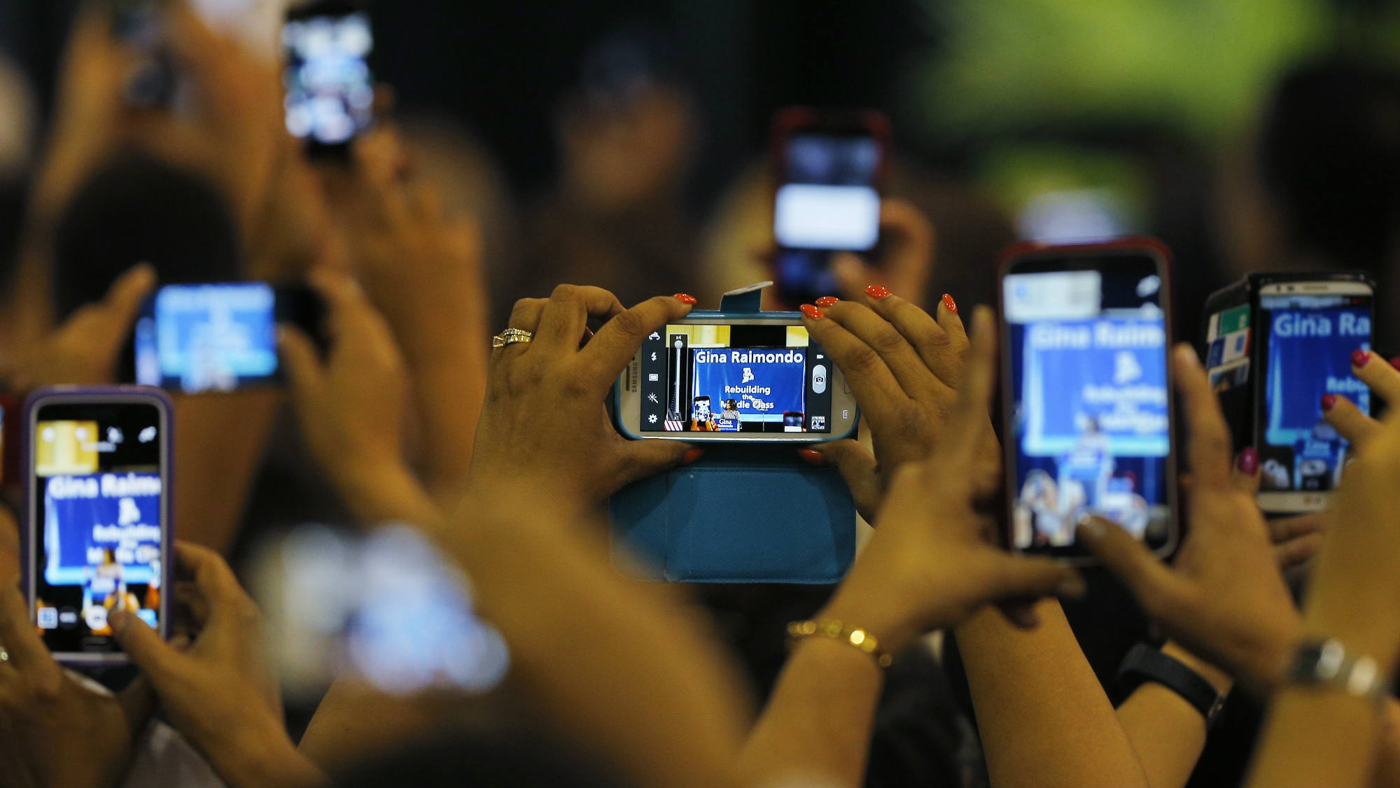 Audience members use their phones to record United States first lady Michelle Obama speaking at a campaign rally for Democratic candidate for Rhode Island Governor Gina Raimondo in Providence, Rhode Island October 30, 2014. REUTERS/Brian Snyder (UNITED STATES - Tags: POLITICS ELECTIONS)