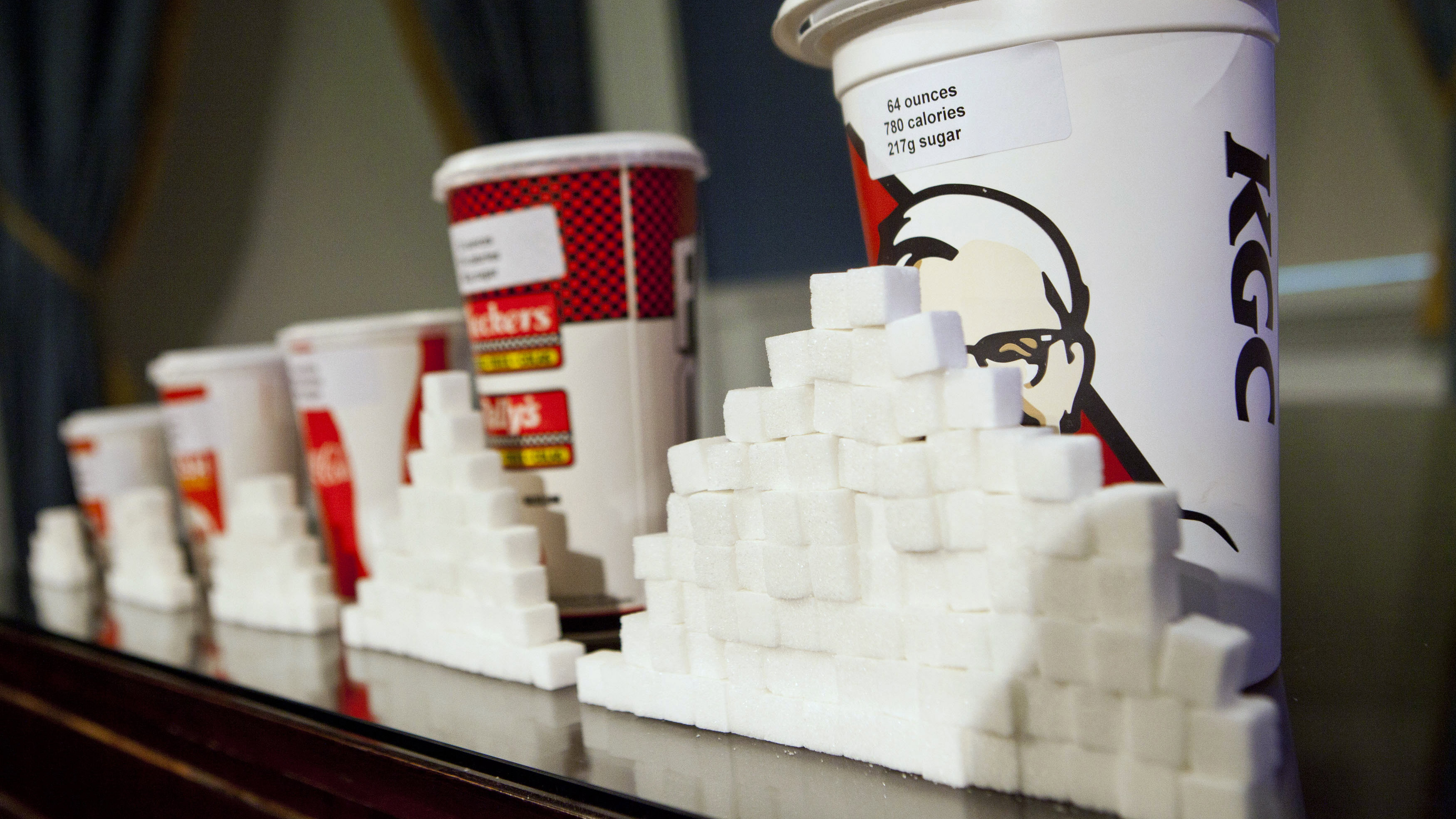 A 64-ounce drink is displayed alongside other soft drink cup sizes at a news conference at City Hall in New York, May 31, 2012. Under a new law proposed by New York City Mayor Michael Bloomberg, all soft drinks over 16 ounces will be banned in restaurants and stores that fall under the jurisdiction of New York City. The proposed law is a part of the mayor's Obesity Task Force initiative and is aimed at lowering city-wide obesity.