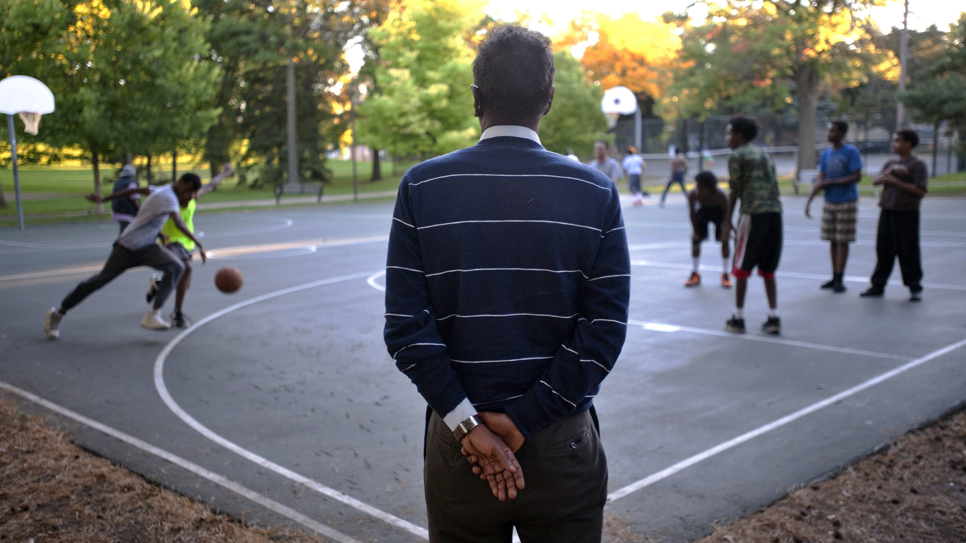 In this Monday, Sept. 22, 2014 photo, Abdirizak Bihi, right, executive director of the Somali Education and Social Advocacy Center, watches kids play basketball at Currie Park in Minneapolis, near a large Somali community in the Cedar Riverside neighborhood. While Bihi strolls through the neighborhood parks, he is on the lookout for anyone who might be trying to recruit the city's young Somalis to join jihad in Syria.