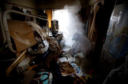A worker for special cleaning makes uses insecticides smoke to kill flies in a garbage-filled flat in Tokyo