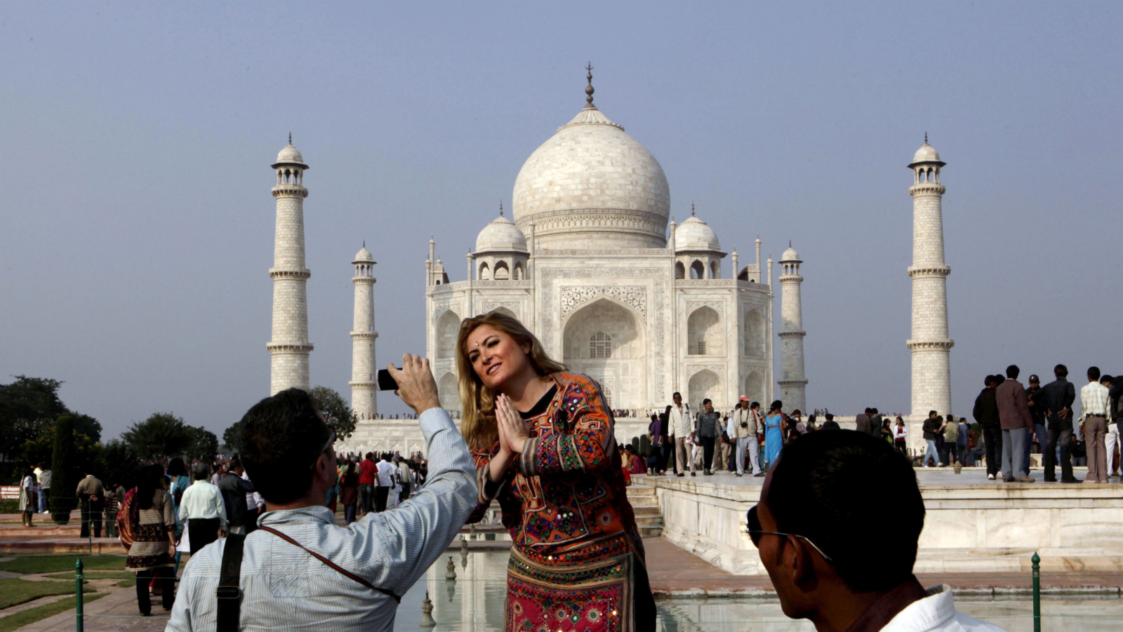 A foreign tourist greets in Indian way as others take her photographs at the Taj Mahal monument, seen behind, in Agra, India, Saturday, Dec. 4, 2010.