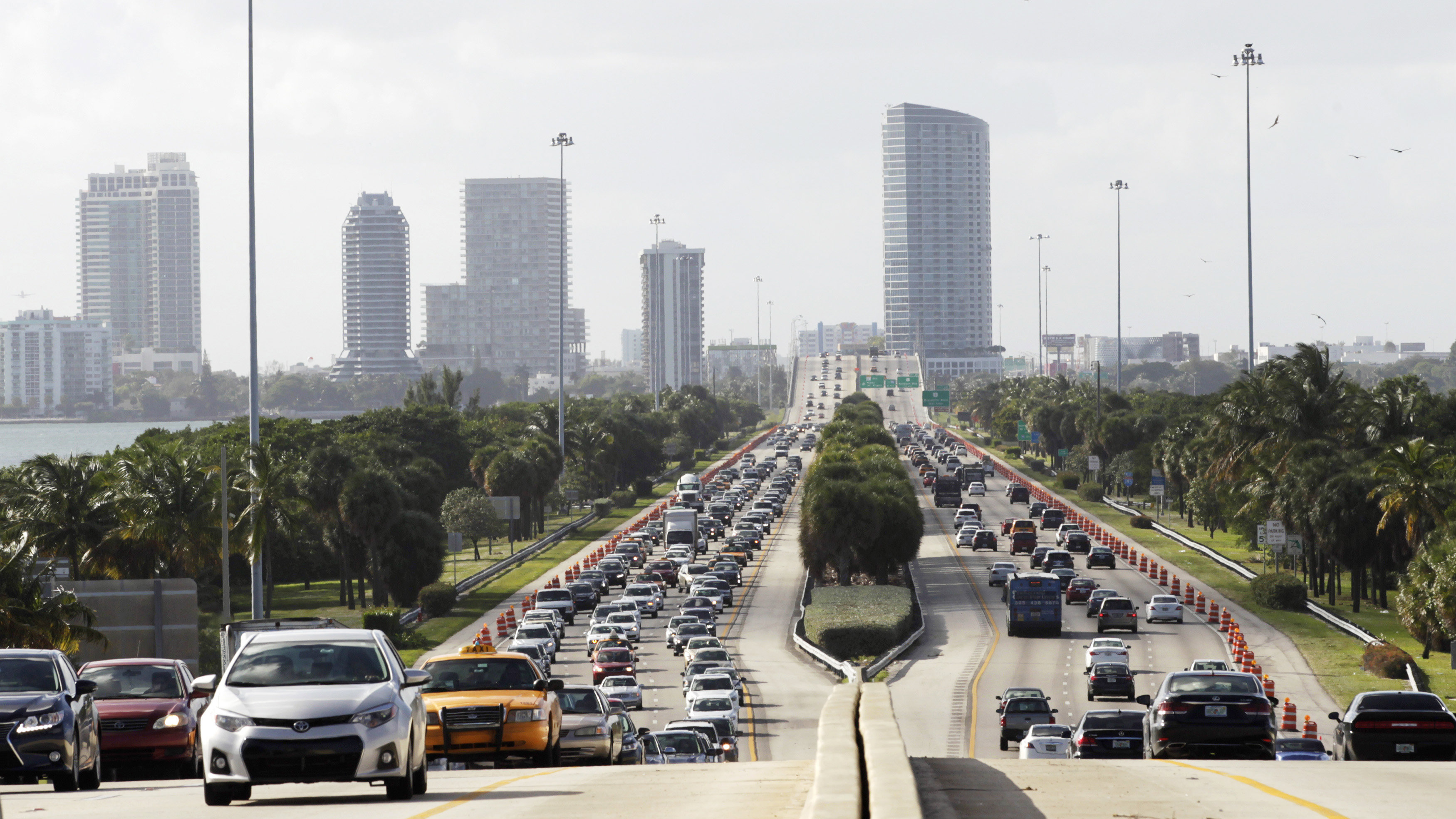 """Traffic leading towards Art Basel on Miami Beach is seen with the skyline of midtown Miami in the background December 4, 2014. An estimated 70,000 art enthusiasts have converged on the city during its annual contemporary """"Art Week,"""" centered around an event called the Art Basel Miami Beach fair. A handful of gallery owners have begun shying away, citing rising rents, few art buyers and condominium development. Still, the graffiti art is welcomed in a city trying to enhance its fun-in-the-sun image and become a more cultured metropolis. Picture taken December 4, 2014. To match Feature USA-MIAMI/GRAFFITI REUTERS/Andrew Innerarity"""