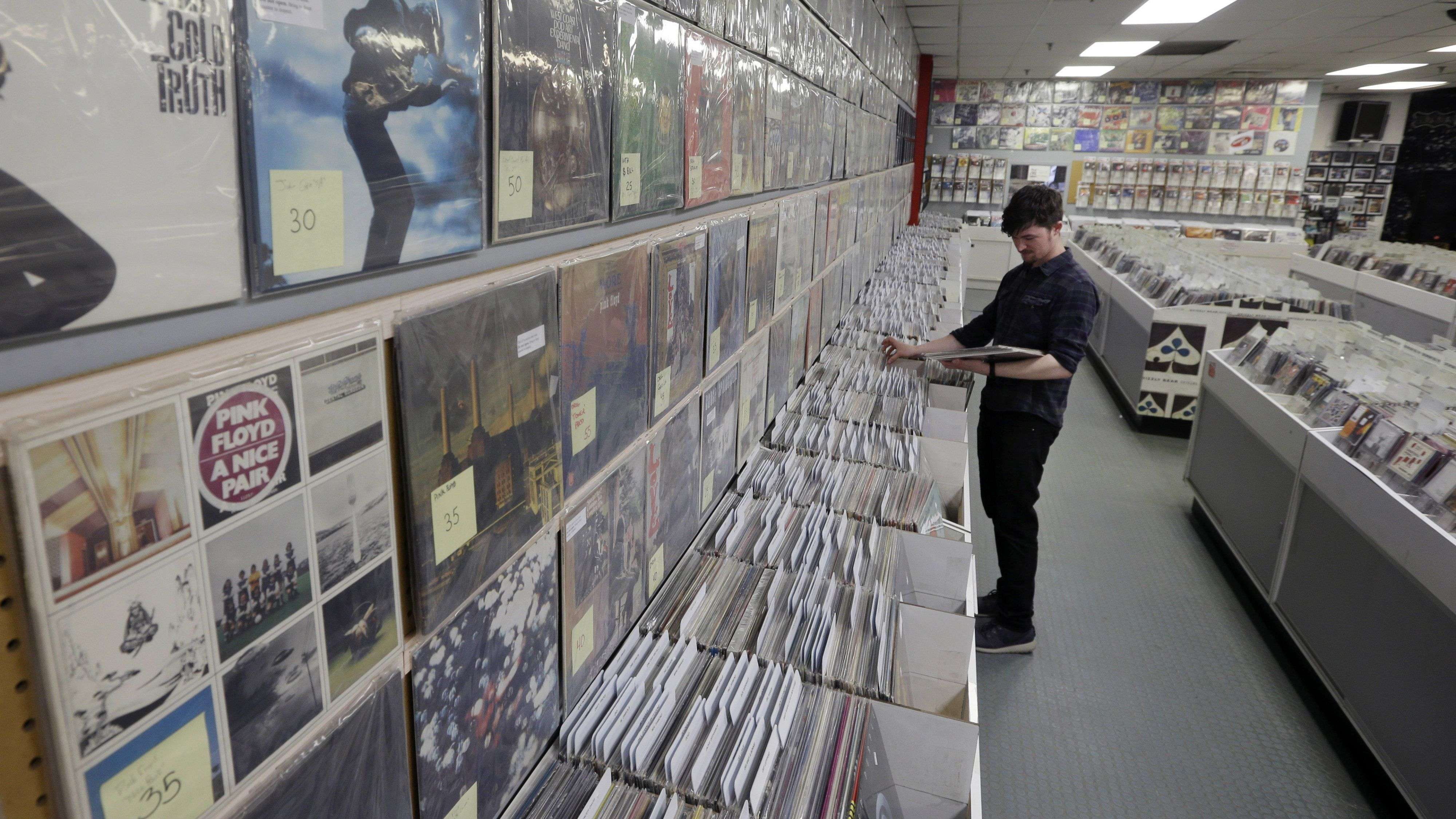 Record clerk Josh Kelly puts LP records in sales bins at Vintage Vinyl Records Tuesday, April 14, 2015
