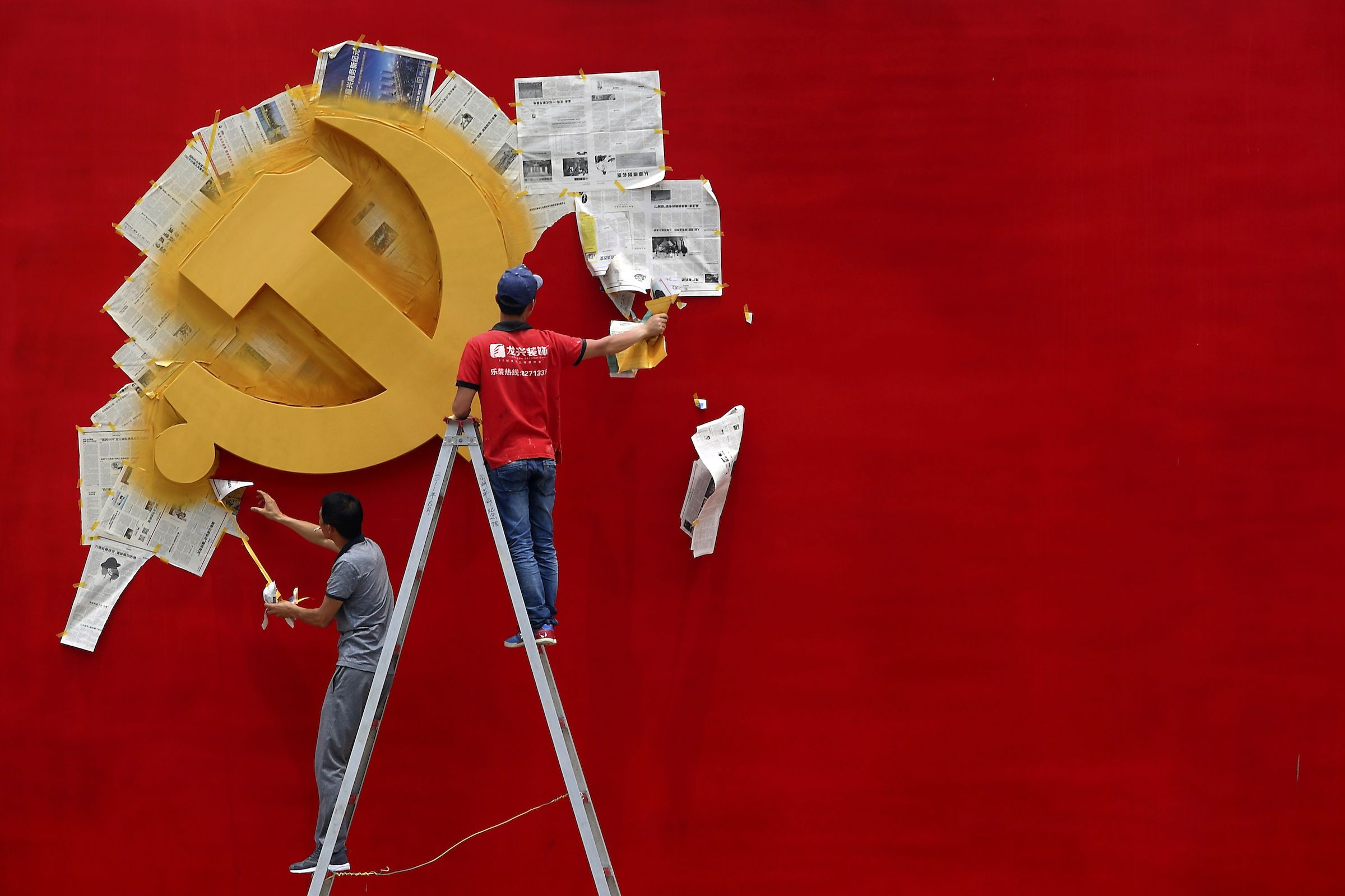 Workers peel papers off a wall as they re-paint the Chinese Communist Party flag on it at the Nanhu revolution memorial museum in Jiaxing, Zhejiang province May 21