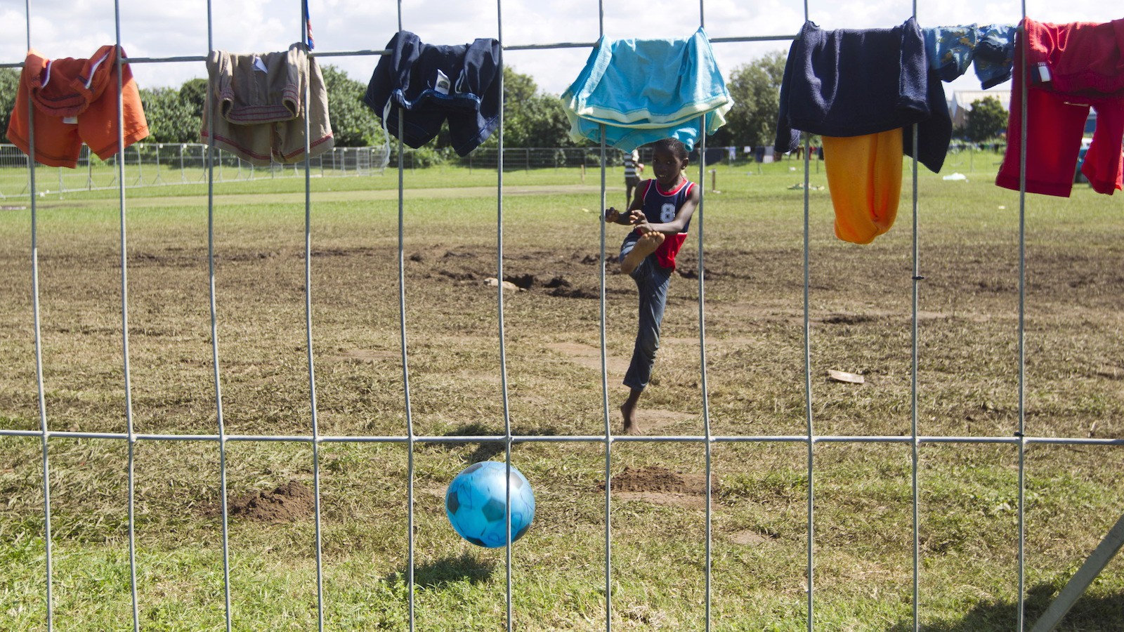 A foreign boy plays soccer at a fenced off sports field in Isipingo, south of Durban, April 9, 2015. Several hundred foreign nationals have sought refuge in the tents after xenophobia driven violence forced them to flee their homes. REUTERS/Rogan Ward - RTR4WOII