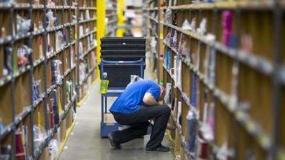 A worker puts together orders at the Amazon logistics center in Brieselang.