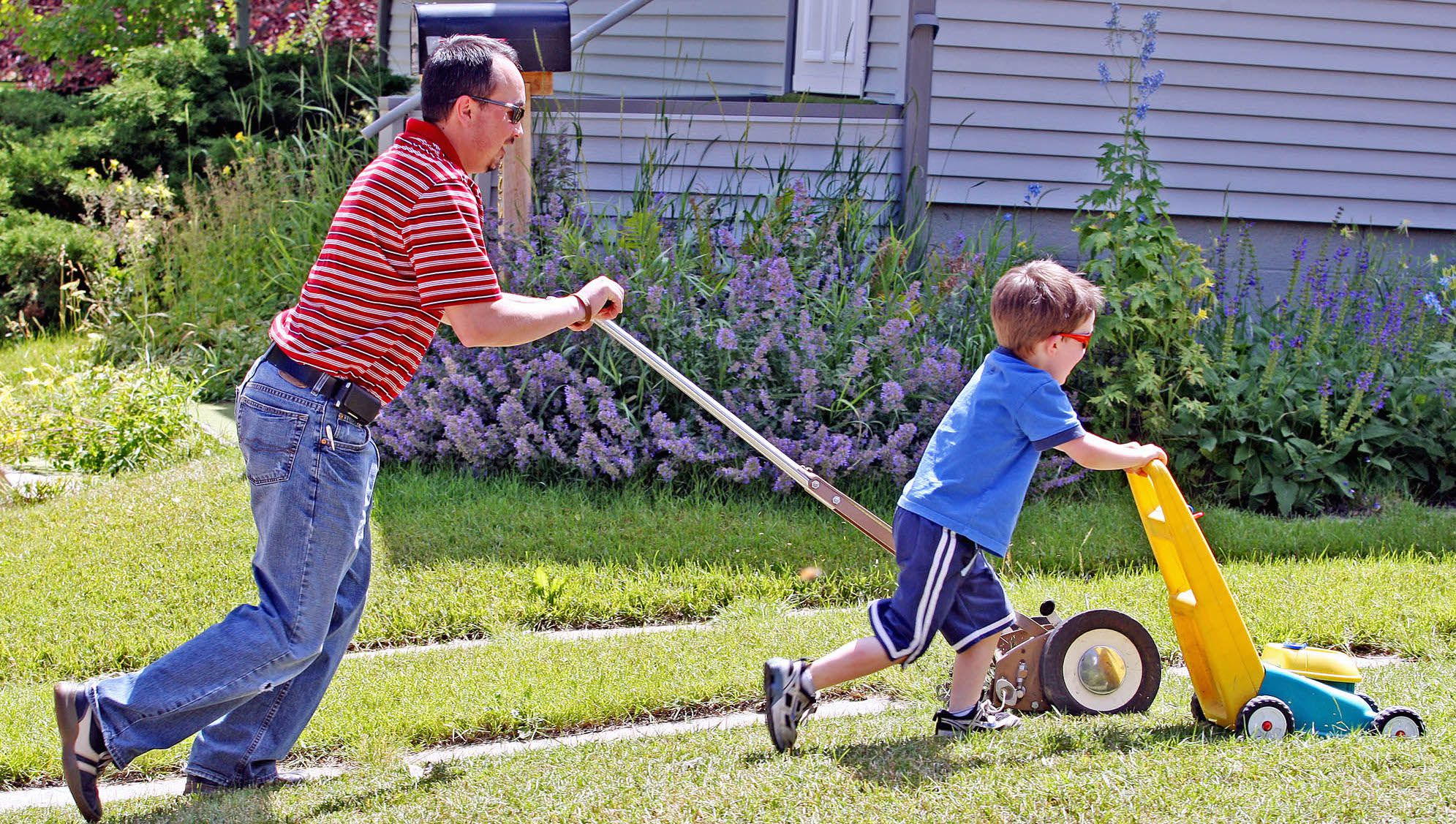 Logan Mack, right, races his father George with a toy lawnmower as the two manicure the family's front lawn Tuesday Aug. 4, 2009 in Laramie, Wyo. (AP Photo/Laramie Boomerang, Andy Carpenean
