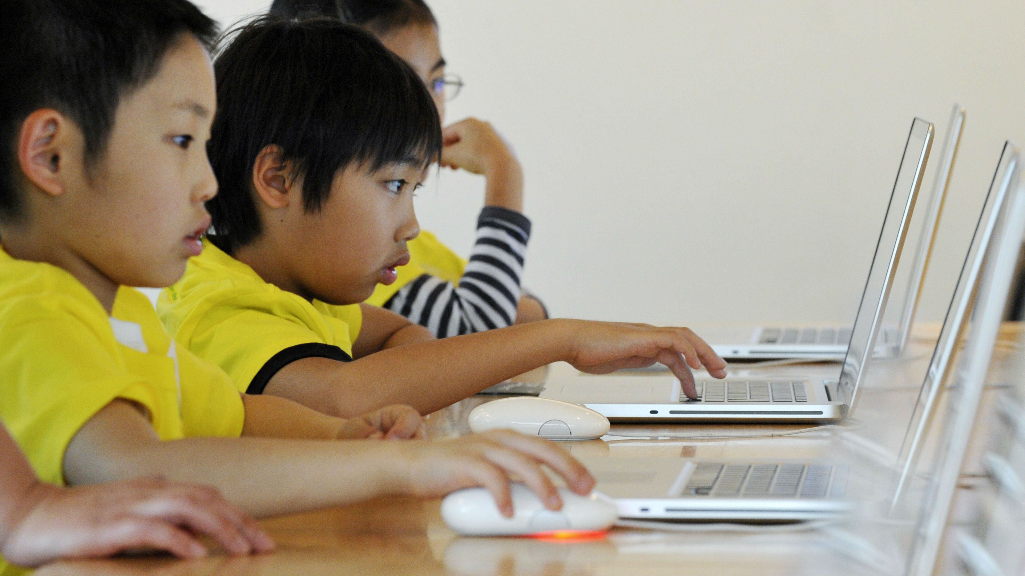 Shotaro Kitamura, 9, right, touches a keyboard as he attends a Kids' day event to learn how to use computers with other elementary school children at Apple Store in Tokyo's Ginza shopping district Tuesday, May 5, 2009, Children's day national holiday. (AP Photo/Katsumi Kasahara)