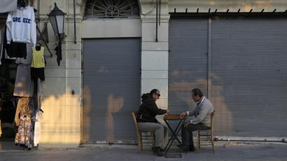 Shop owners play backgammon in the Plaka area of central Athens.