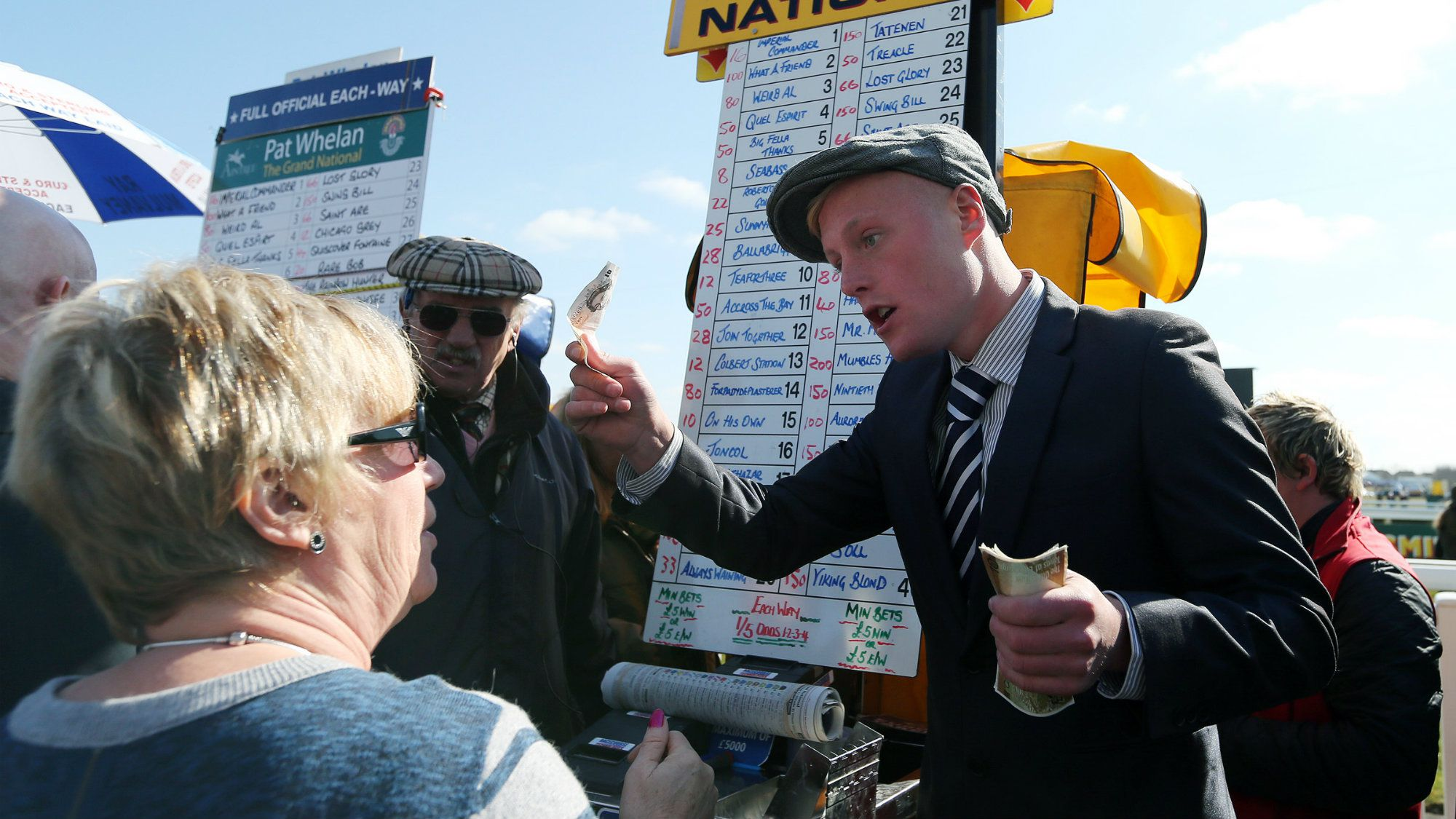 A race goer waits to make a bet to a bookmaker with the odds for the horses which are running in the Grand National horse race.
