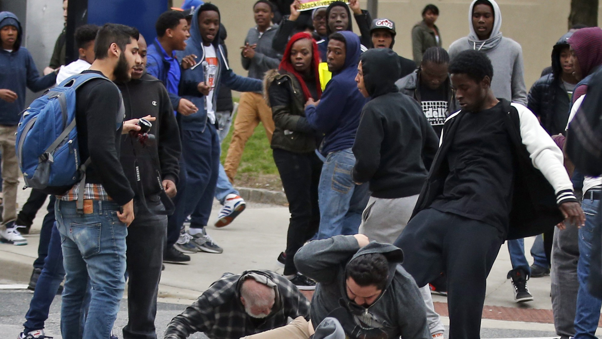 A man is kicked as he attempts to get up after being knocked down, following a march to City Hall for Freddie Gray, Saturday, April 25, 2015 in Baltimore.