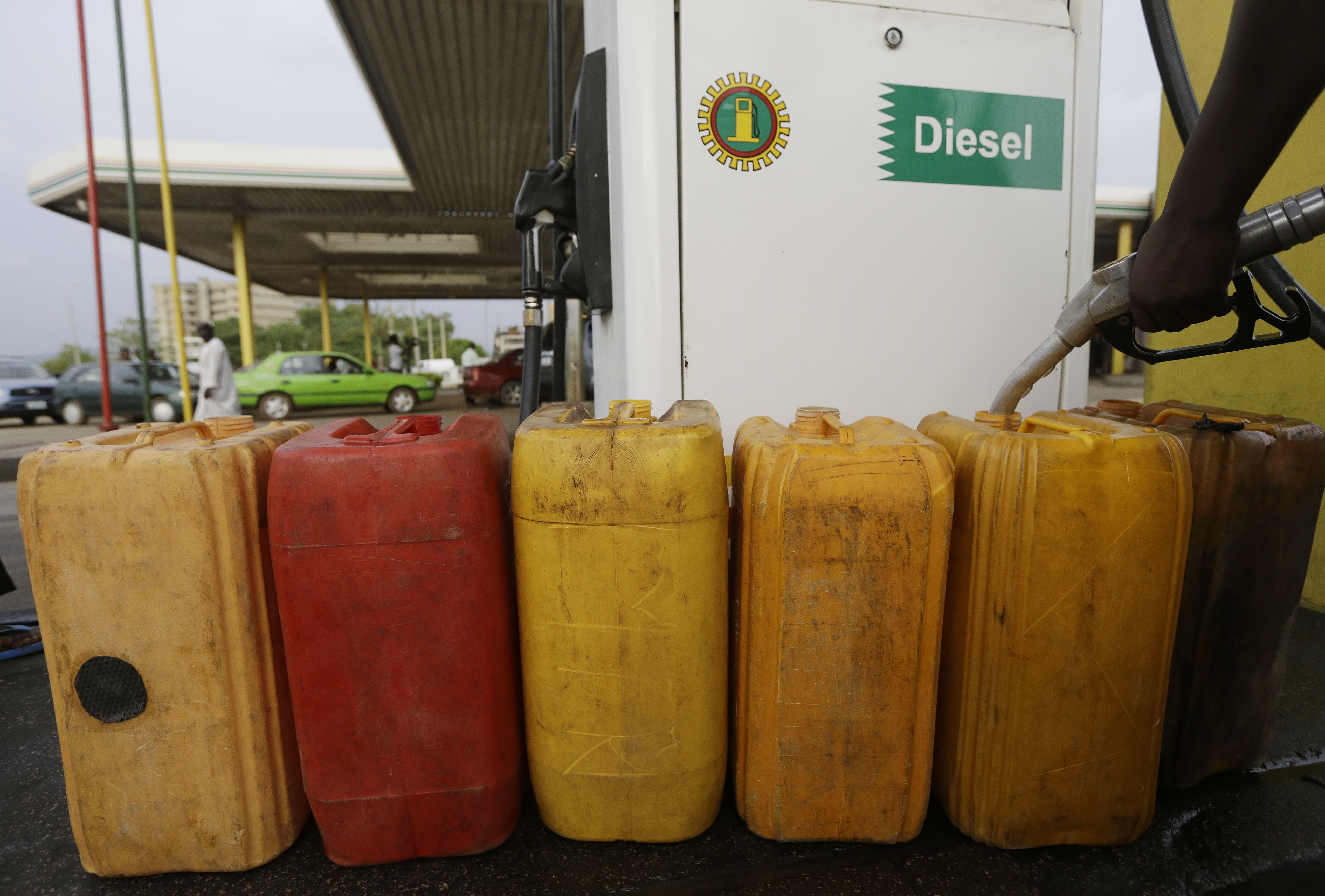 A man fills containers with diesel at a petrol station in Abuja