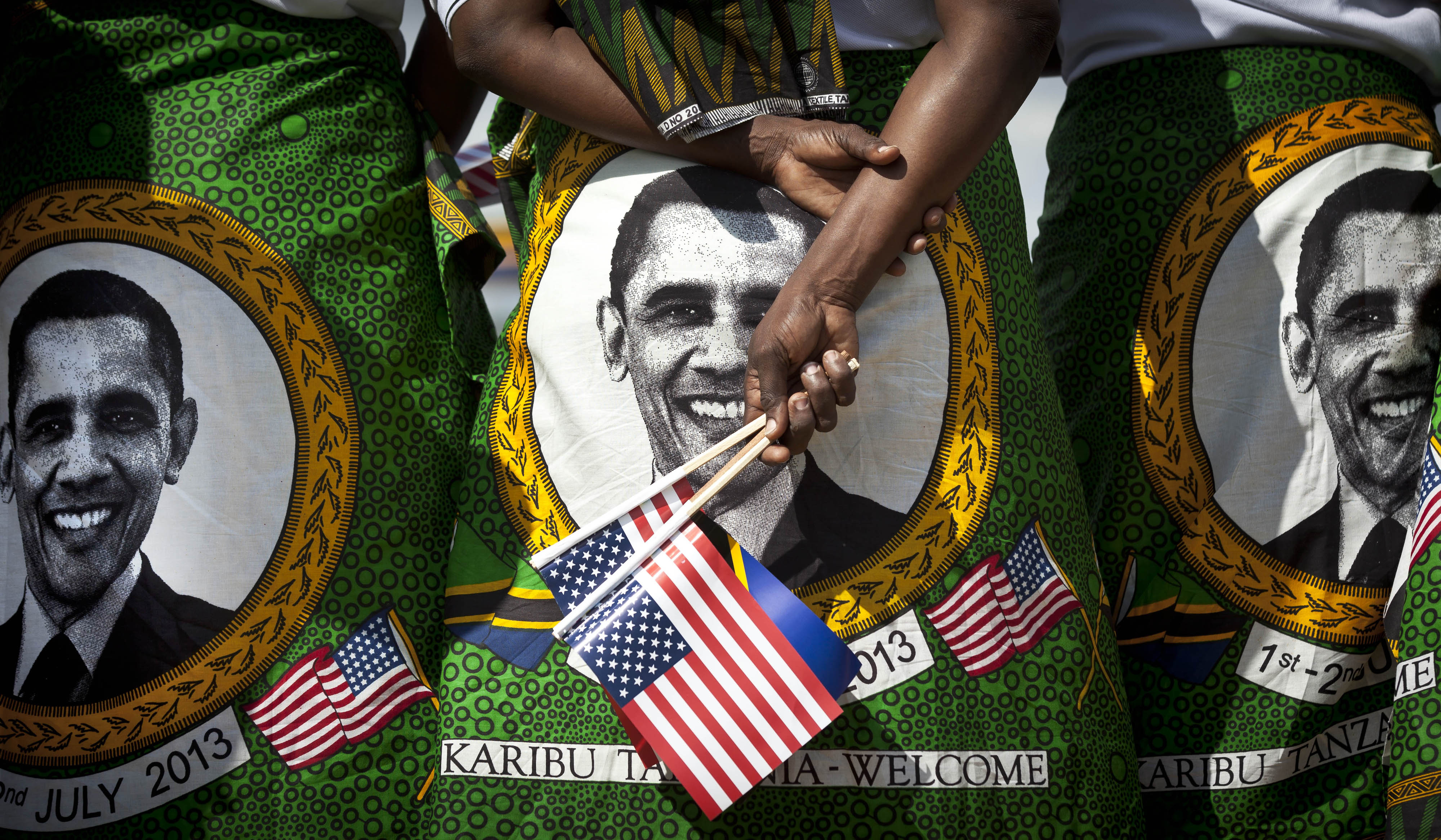 Women from a welcoming group wearing skirts and shawls with the face of  President Barack Obama at Julius Nyerere airport at the end of his weeklong visit to Africa in 2013, in Dar es Salaam, Tanzania.