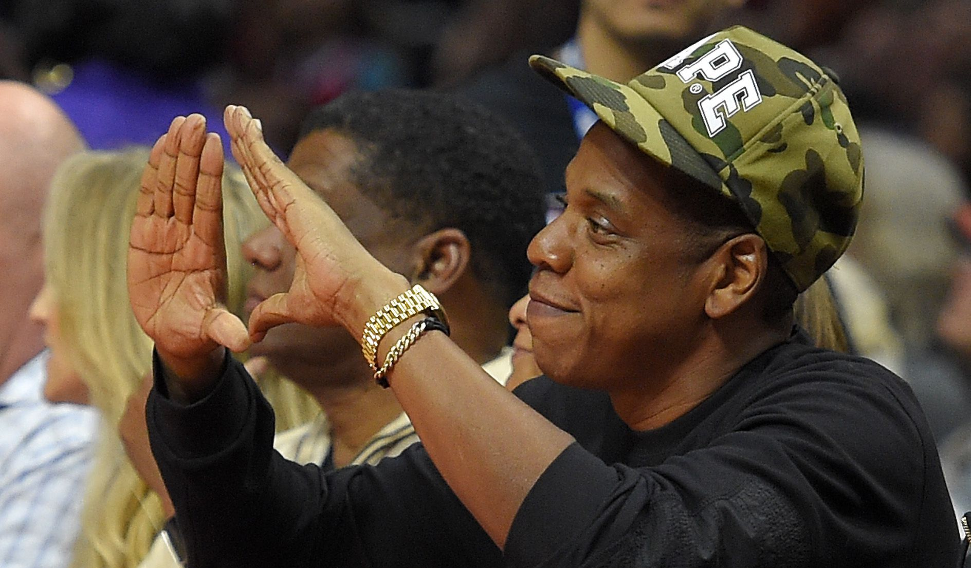 Rapper Jay-Z gestures during the first half of an NBA basketball game between the Los Angeles Clippers and the Cleveland Cavaliers, Friday, Jan. 16, 2015, in Los Angeles.