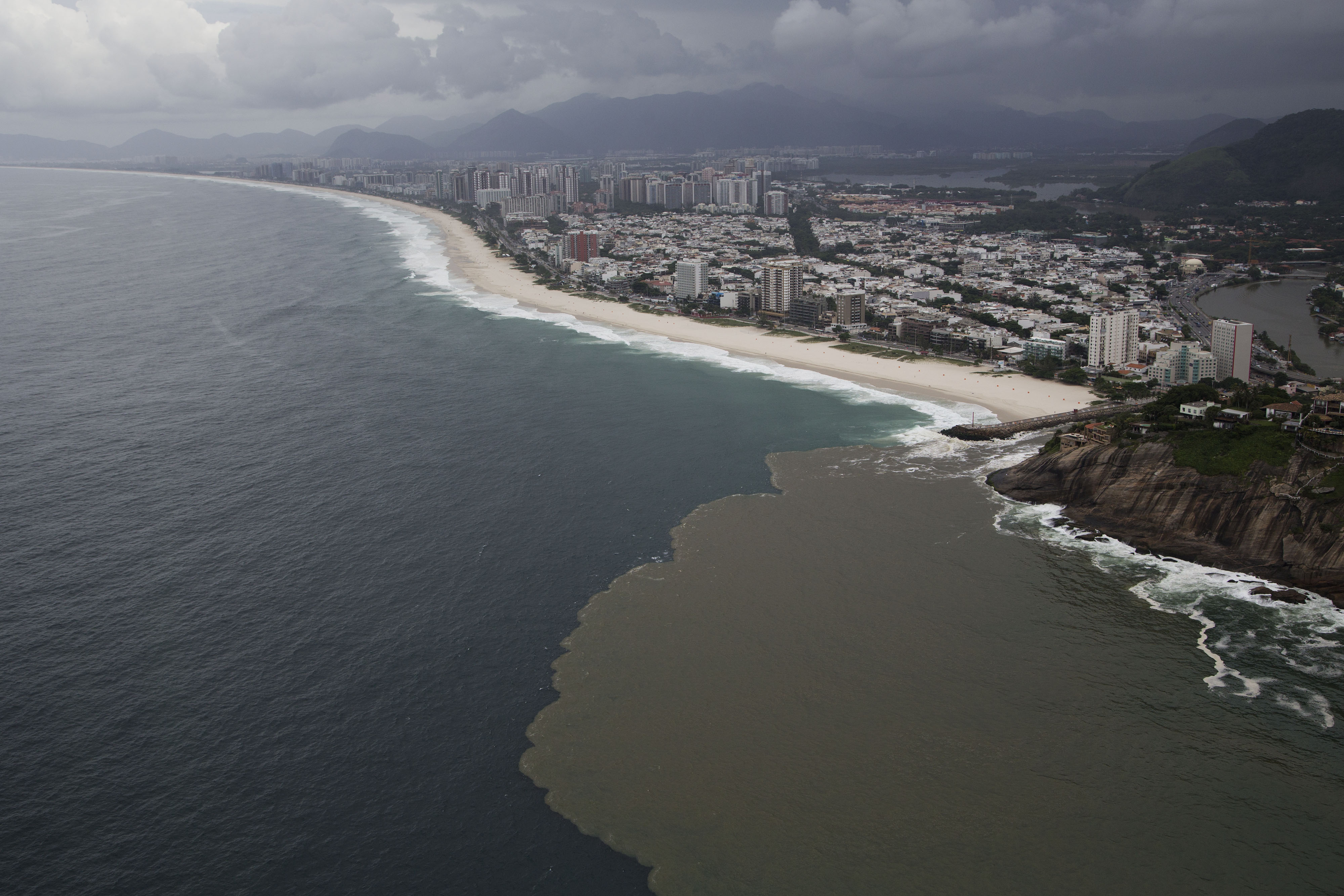 """This aerial view shows polluted water flowing from the Barra channel to the Barra beach, in Rio de Janeiro, Brazil, Monday, March 23, 2015. Rio de Janeiro's mayor acknowledged in a television interview Monday that the run-up to the 2016 games has proven a """"wasted opportunity"""" to clean up the city's blighted waterways. (AP Photo/Felipe Dana)"""