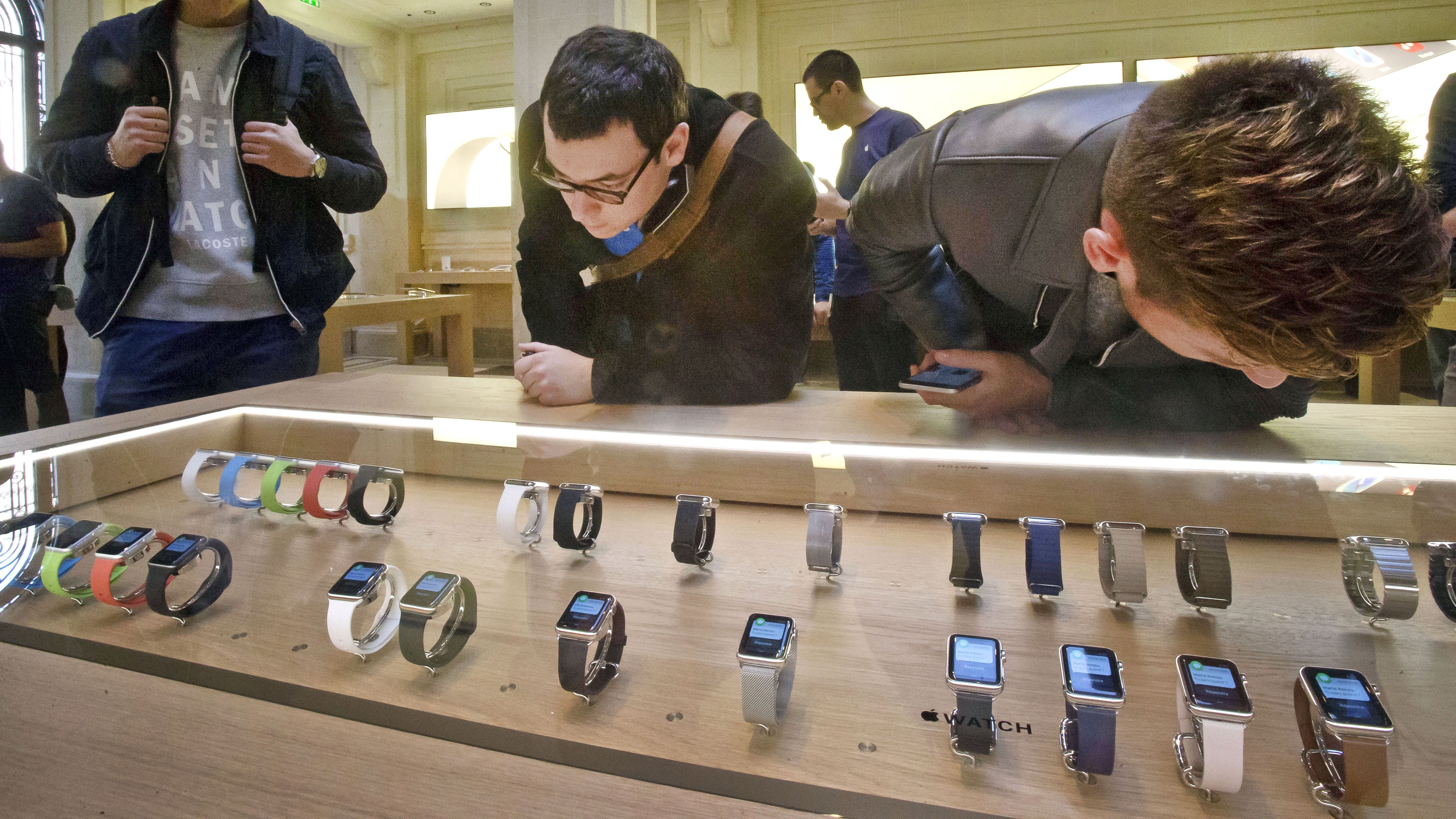 Customers examine the new Apple watches presented at the Paris Opera Apple store Friday April 10, 2015. From Beijing to Paris and San Francisco, the Apple Watch made its world debut Friday. Customers were invited to try them on in stores and order them online. (AP Photo/Michel Euler)