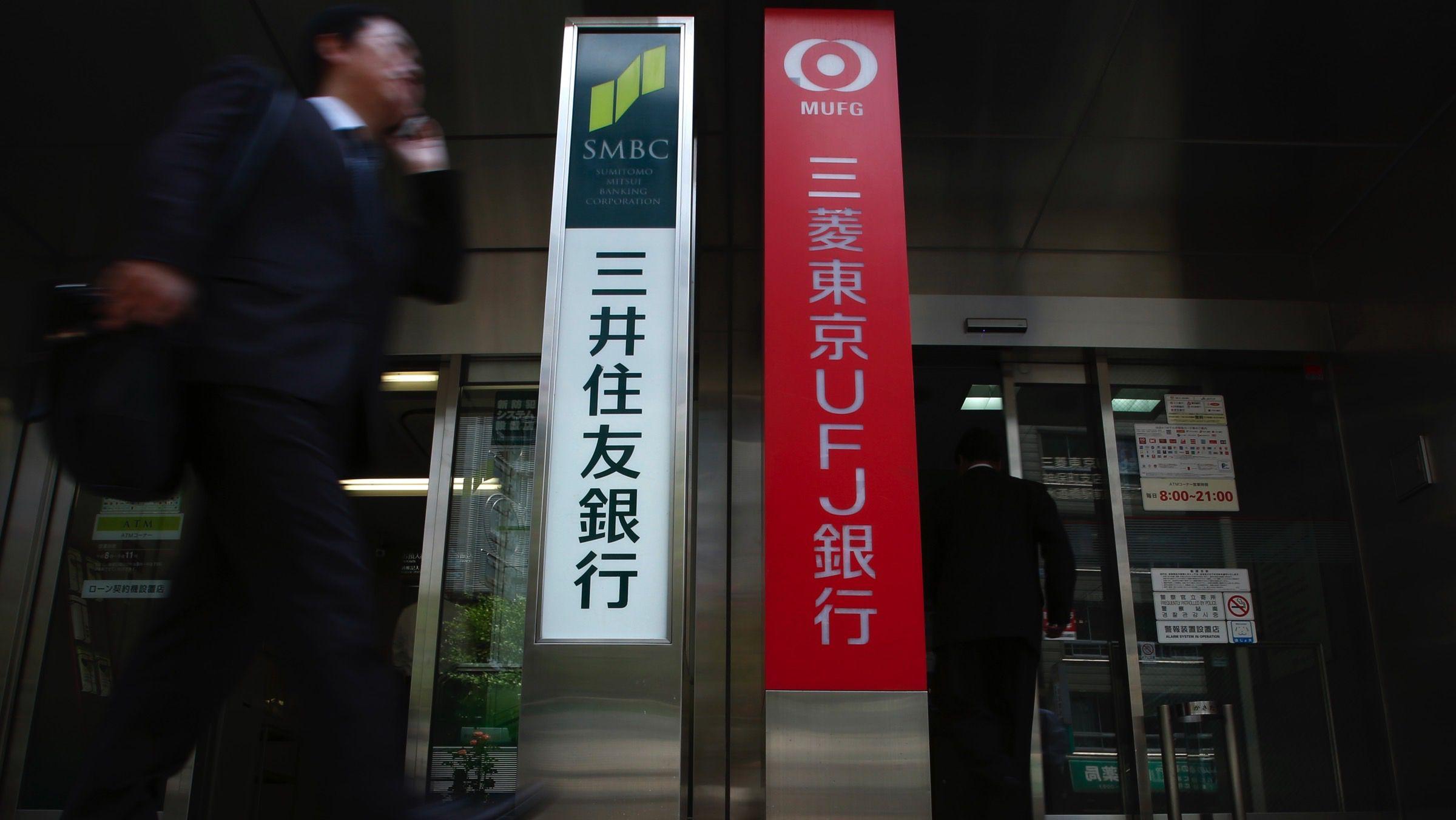 A man walks past ATM machines booth of Japan's mega banks, Sumitomo Mitsui Banking Corporation and Bank of Tokyo-Mitsubishi UFJ, in Tokyo