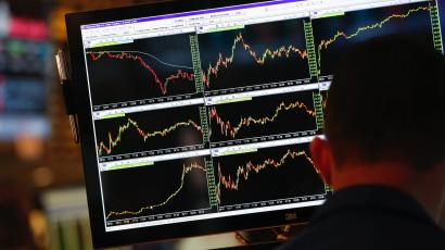 A screen displays stock charts while a trader works at his post on the floor at the New York Stock Exchange, May 30, 2013.