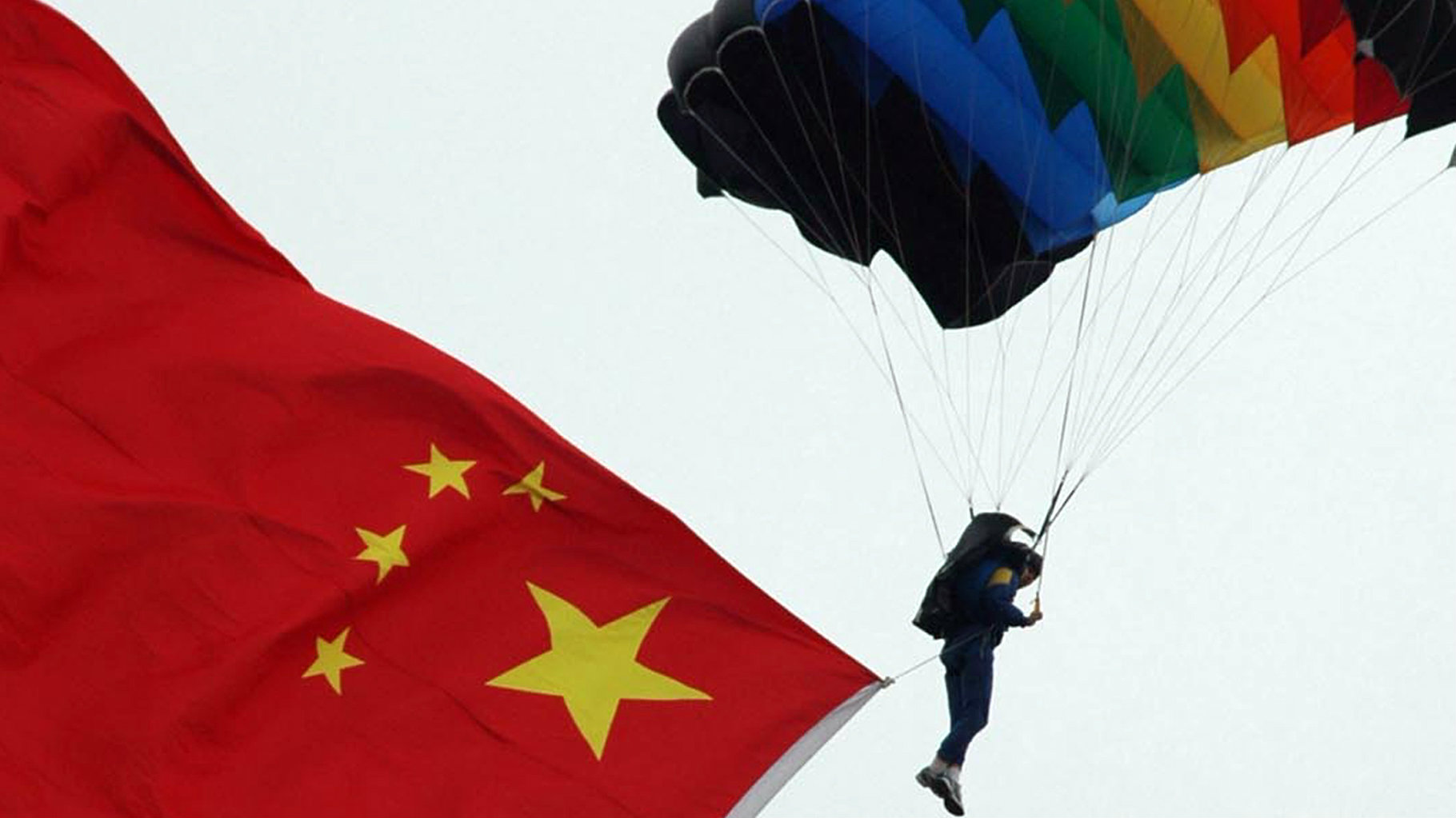A soldier carrying a Chinese national flag parachutes over a stadium in Wuhu, east China's Anhui province, September 25, 2005. Various activities are held nationwide to celebrate the upcoming National Day that falls on October 1, 2005. Picture taken September 25, 2005. CHINA OUT REUTERS/China Newsphoto PP05090328