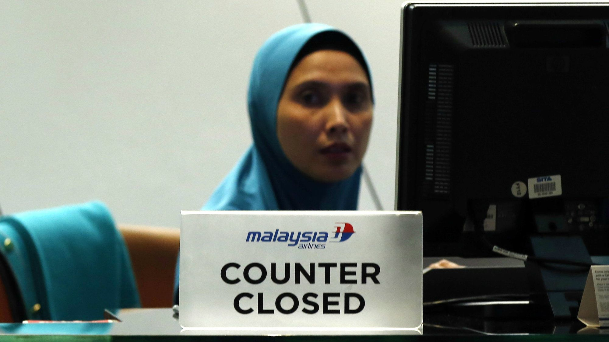 A staff member sits behind a closed Malaysia Airlines desk at Kuala Lumpur International Airport.