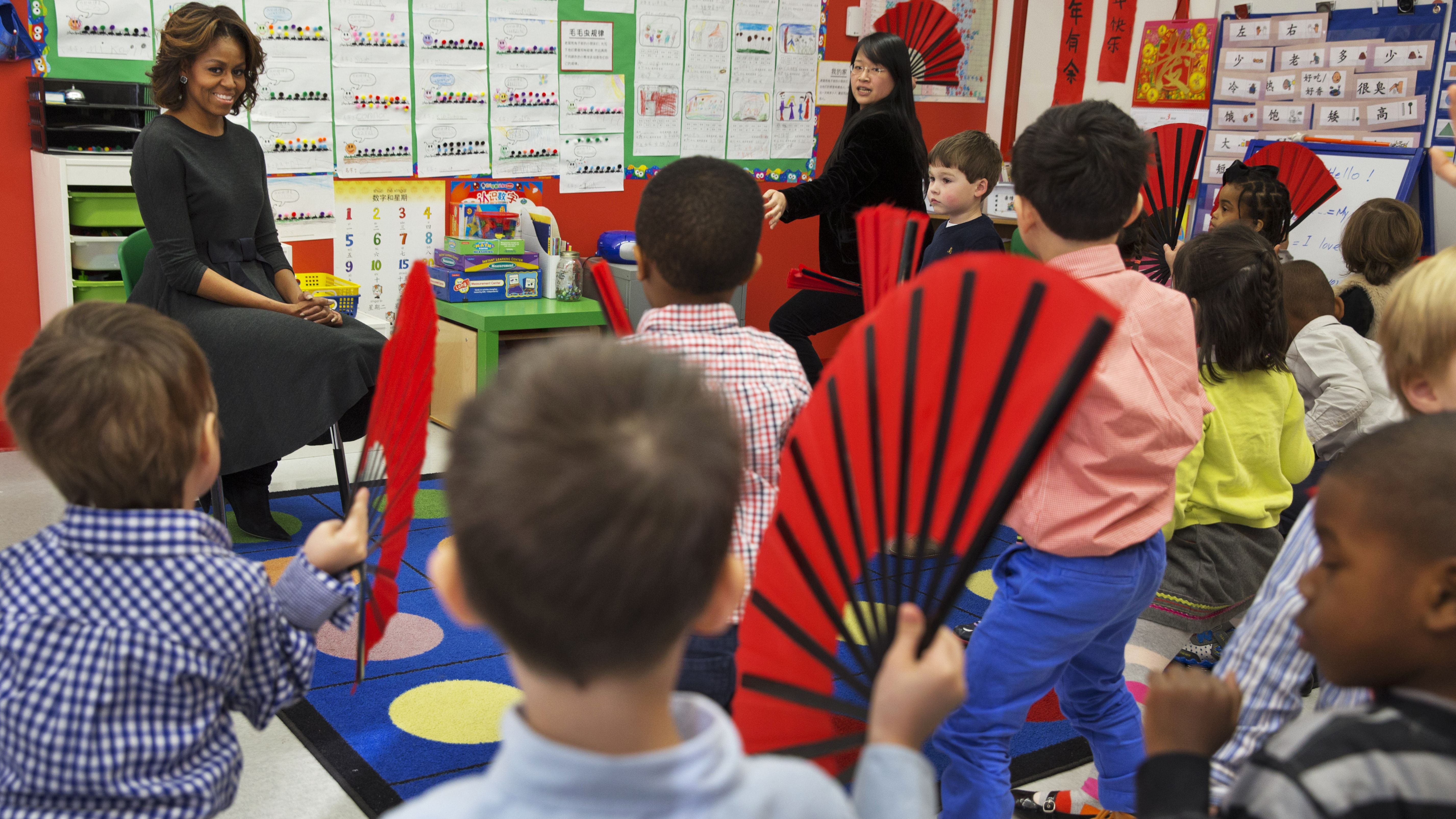 First lady Michelle Obama watches as pre-Kindergarten students perform a fan dance at Yu Ying Public Charter School in Washington, Tuesday, March 4, 2014. Later in March the first lady is expected to take a trip to China along with her daughters and mother. (AP Photo/Jacquelyn Martin)
