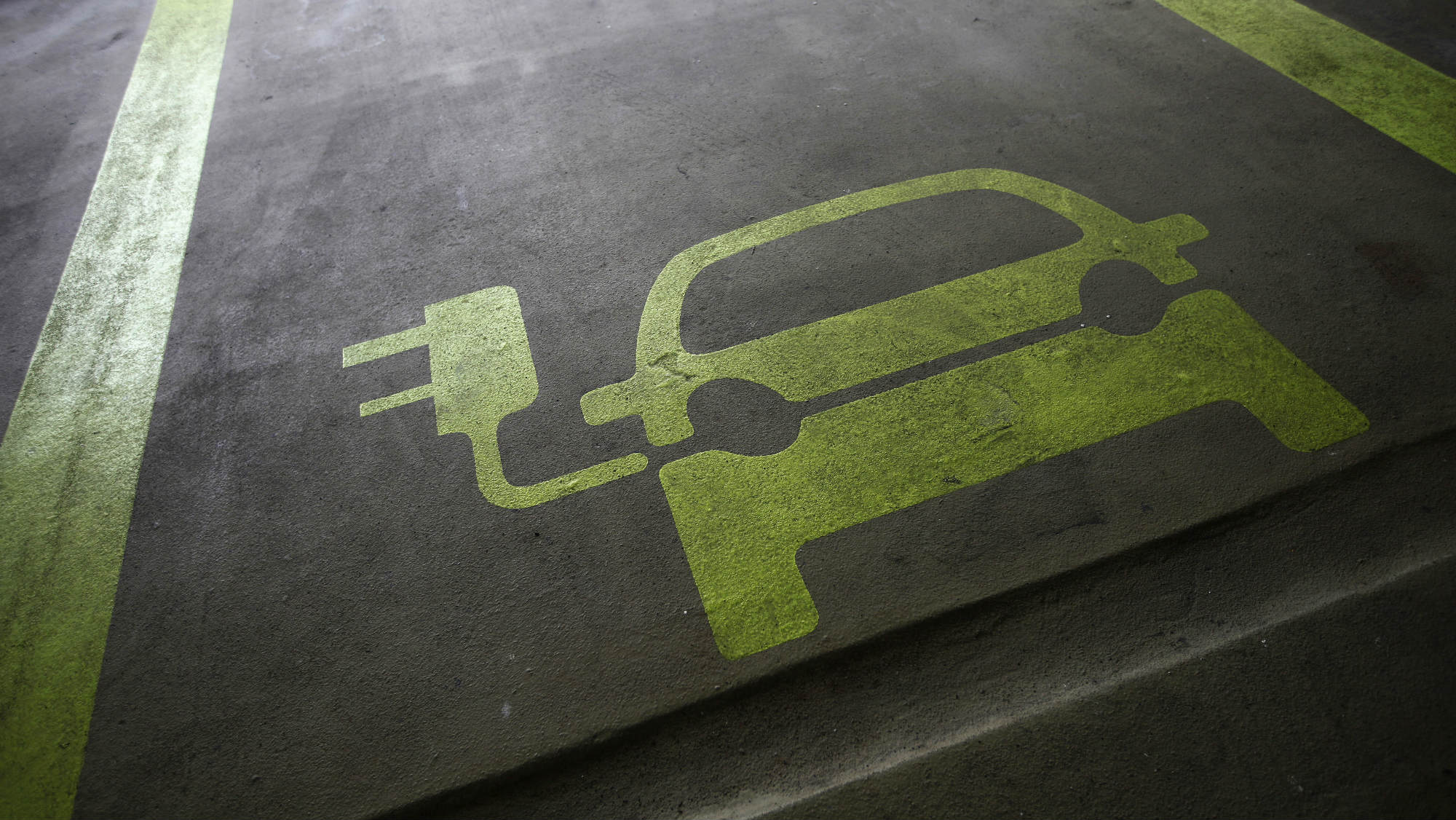 A sign is painted on a parking space for electric cars inside a car park in Hong Kong January 29, 2012. Many of the headlines out of autoshows in the past couple of years have been captured by the launch of electric cars such as Nissan's Leaf, the Tesla sports car, plug-ins like General Motors' Chevrolet Volt, and the latest incarnation of the Toyota Prius. Other manufacturers including BMW, Rolls Royce and Porsche have presented electric-powered prototypes. On the basis of this, one could be forgiven for thinking the auto industry is betting big on electric power. Yet few auto executives share the optimism of Renault and Nissan chief executive Carlos Ghosn who has repeatedly said he sees electric vehicles making up 10 percent of all sales in 2020. A survey of 200 auto industry executives conducted by KPMG released on Monday gave an average forecast for electric vehicles to account for 6-10 percent of global auto sales in 2025, more bullish than oil companies BP and Exxon who expect electric cars to make up no more than 4-5 percent of all cars globally in 20-30 years. Picture taken January 29, 2012. To match Insight ELECTRIC-CAR/BIG OIL REUTERS/Tyrone Siu (CHINA - Tags: BUSINESS ENERGY ENVIRONMENT SCIENCE TECHNOLOGY)