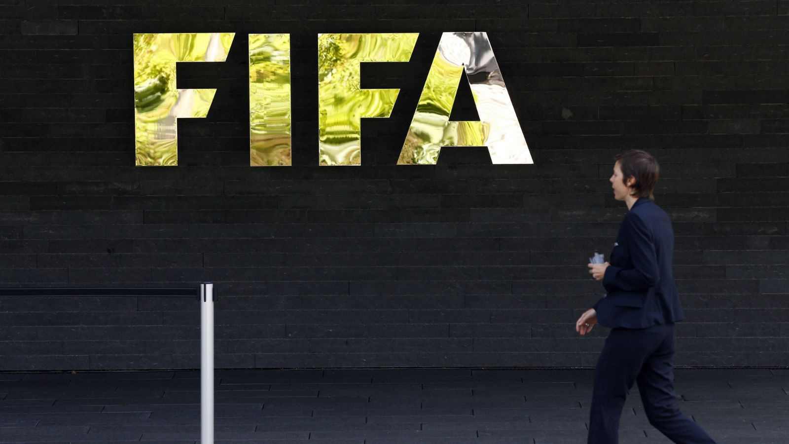 A staff walks past a logo of soccer's international governing body FIFA at their headquarters in Zurich, Switzerland, May 27, 2015. Six soccer officials were arrested in Zurich on Wednesday and detained pending extradition to the United States over suspected corruption at soccer's governing body FIFA, the Swiss Federal Office of Justice said in a statement.