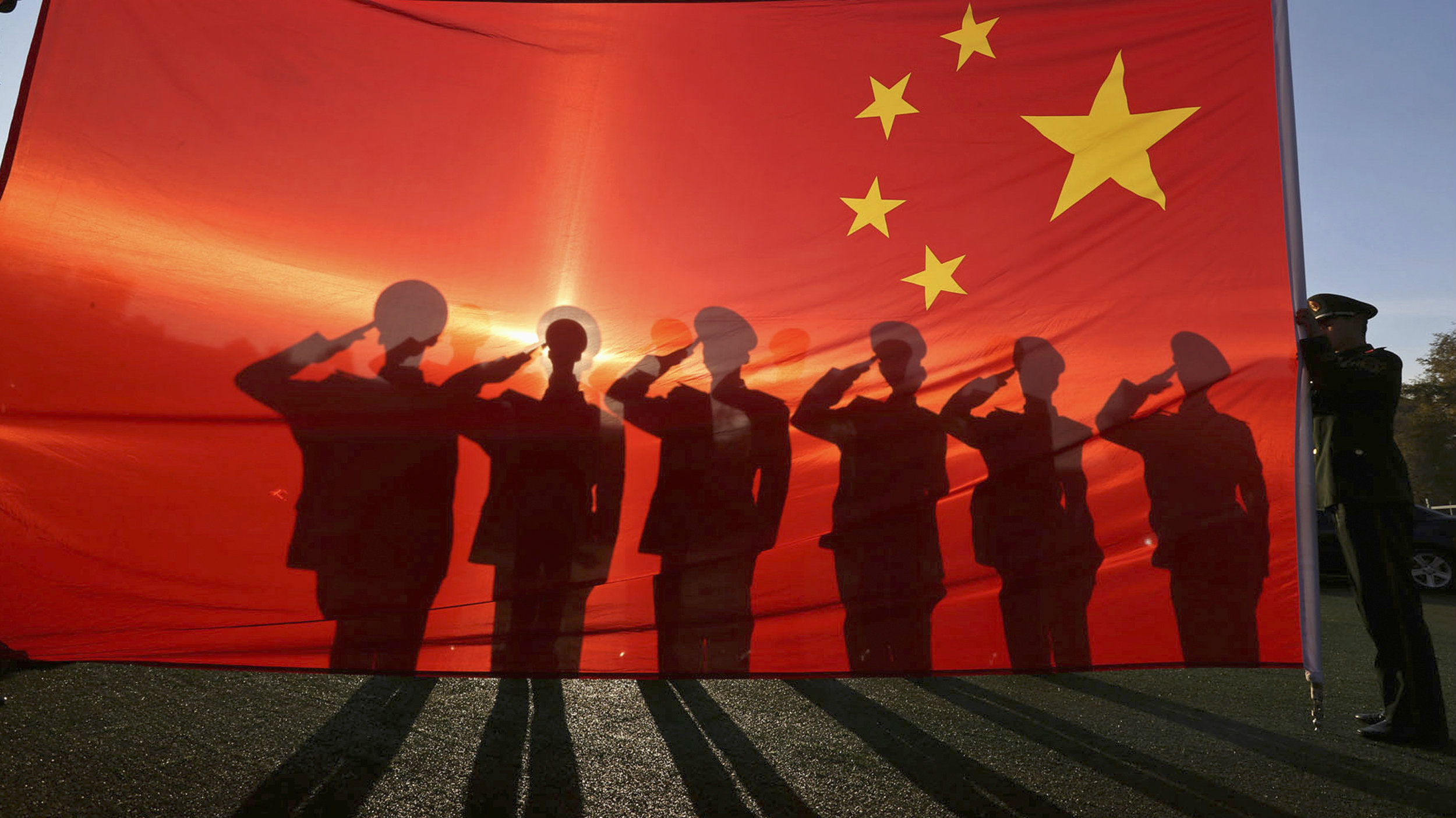 Retired paramilitary policemen, who conduct the daily national flag raising and lowering ceremony on Tiananmen Square, salute to a Chinese national flag during a farewell ceremony in Beijing, November 24, 2014.