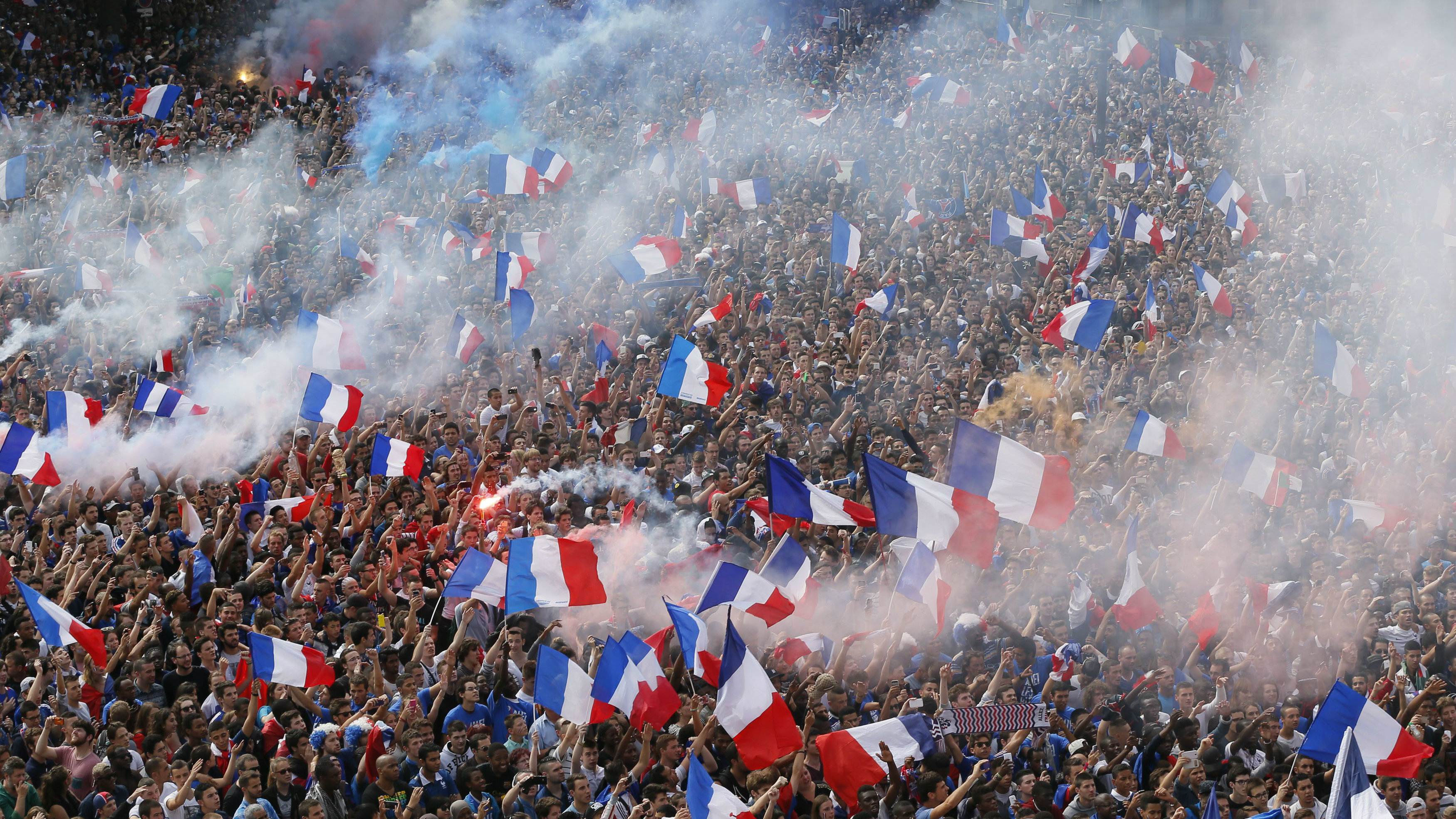 France team fans wave flags as they gathe to watch the 2014 World Cup quarter-finals soccer match between France and Germany at the Maracana stadium in Rio de Janeiro, on a giant screen outside the city hall in Paris July 4, 2014.