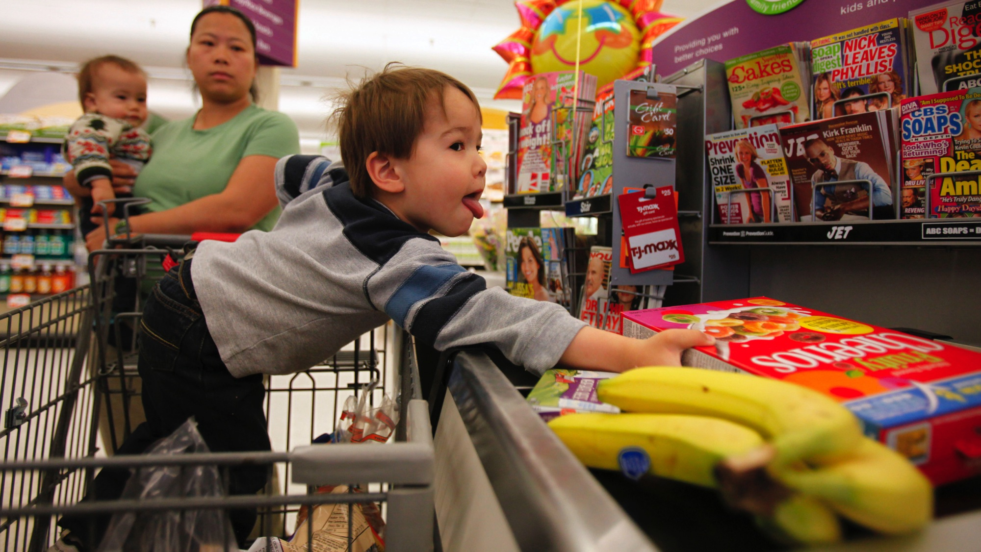 In this April 6, 2009 photo, A.J. Wynne, 3, of Chevy Chase, Md., loads groceries onto the belt as his mother Becky Wynne holds Henry Wynne, 11 months, at a Giant grocery store in Silver Spring, Md. As the recession drags on, moms and dads are figuring out ways to dote without opening their wallets. They're nixing fancy birthday parties, music lessons, sports leagues and gifts for their children. (AP Photo/Jacquelyn Martin)