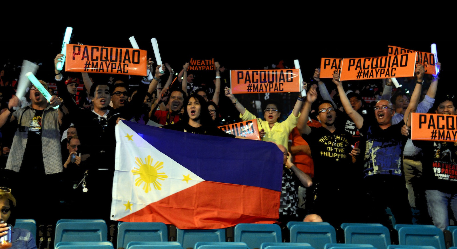 epa04729059 Fans of Filipino boxer Manny Pacquiao hold signs and wave the Philippines national flag prior to the weigh-in with US boxer Floyd Mayweather Jr at MGM Grand Garden Arena in Las Vegas, Nevada, USA, 01 May 2015.  Pacquiao will fight Mayweater Jr. for the WBC welterweight title bout  on 02 May in Las Vegas.  EPA/MICHAEL NELSON