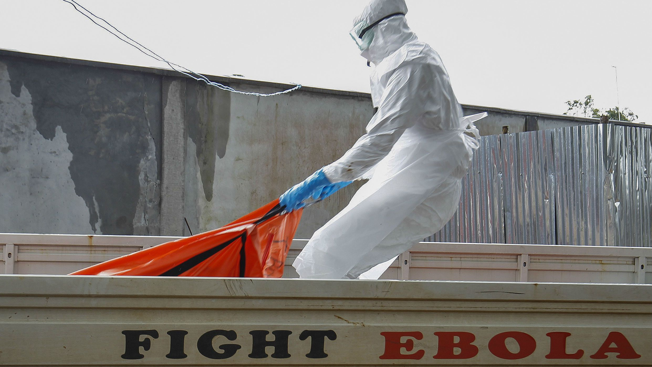 epa04739376 (FILE) A file picture dated 13 October 2014 shows a Liberian health worker in a burial squad drags an Ebola victim's body for cremation from the ELWA treatment center in Monrovia, Liberia. Liberia is declared free from Ebola on 09 April 2015 after 42 days without a new case, the medical charity Medecins Sans Frontieres reported, but urged vigilance until the worst-ever recorded outbreak of the virus is extinguished in neighbouring Guinea and Sierra Leone. The last patient in Liberia died on 27 March 2015, and by 09 April 2015 the nation reaches the official World Health Organization (WHO) standard of 42 days without a new Ebola case. A total of 10,980 people have been killed and more than 26,500 people were infected by Ebola disease since the outbreak erupted in a remote area of Guinea in December 2013, according to WHO. EPA/AHMED JALLANZO