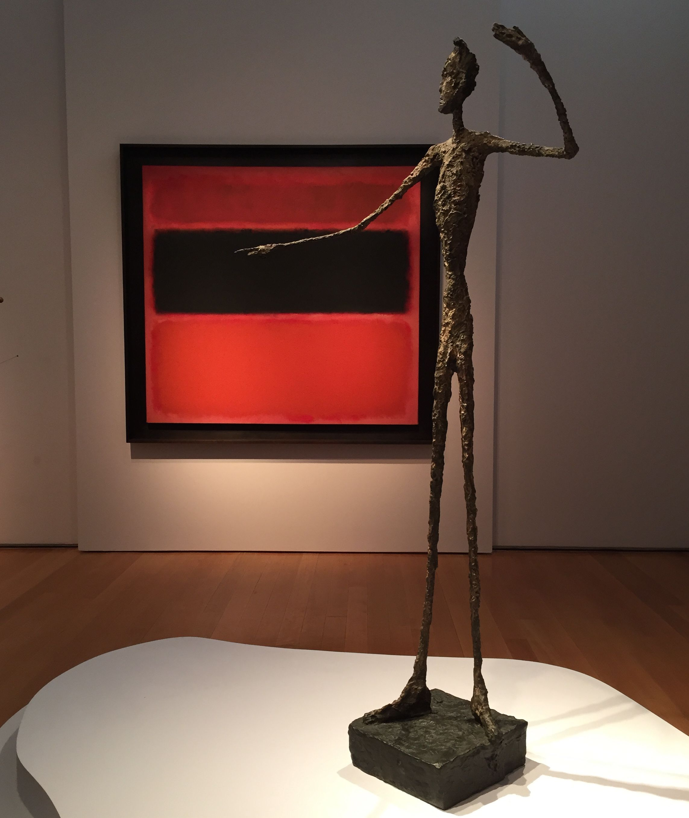 """Alberto Giacometti's """"L'homme au doigt"""" with Mark Rothko's """"No. 36 (Black Stripe)"""" in the background"""
