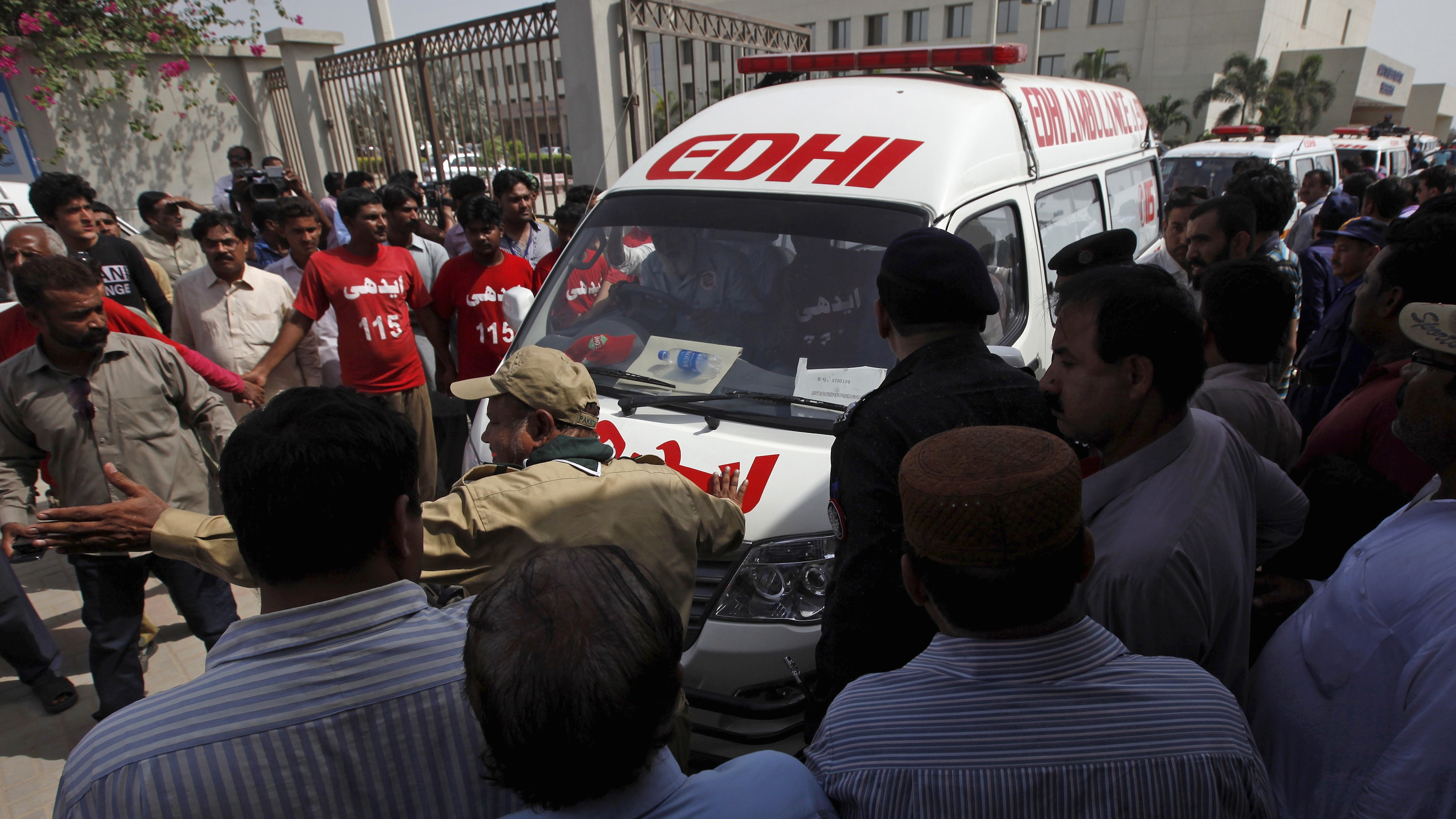 People gather as rescue workers and volunteers makes way for ambulances, carrying bodies of the victims of an attack on a bus, as they move outside the hospital in Karachi, Pakistan, May 13, 2015