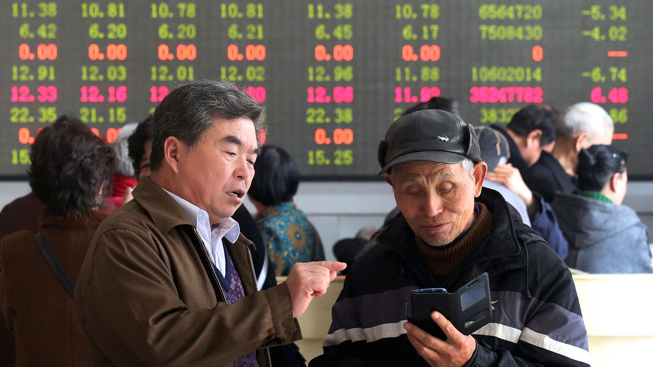 Investors talk in front of an electronic board showing stock informations at a brokerage house in Kaifeng, Henan province, April 9, 2015. China stocks lost ground on Thursday, as mainland investors rushed to buy relatively cheaper Hong Kong shares, but some key sectors such as property found support from bargain hunters. REUTERS/China Daily