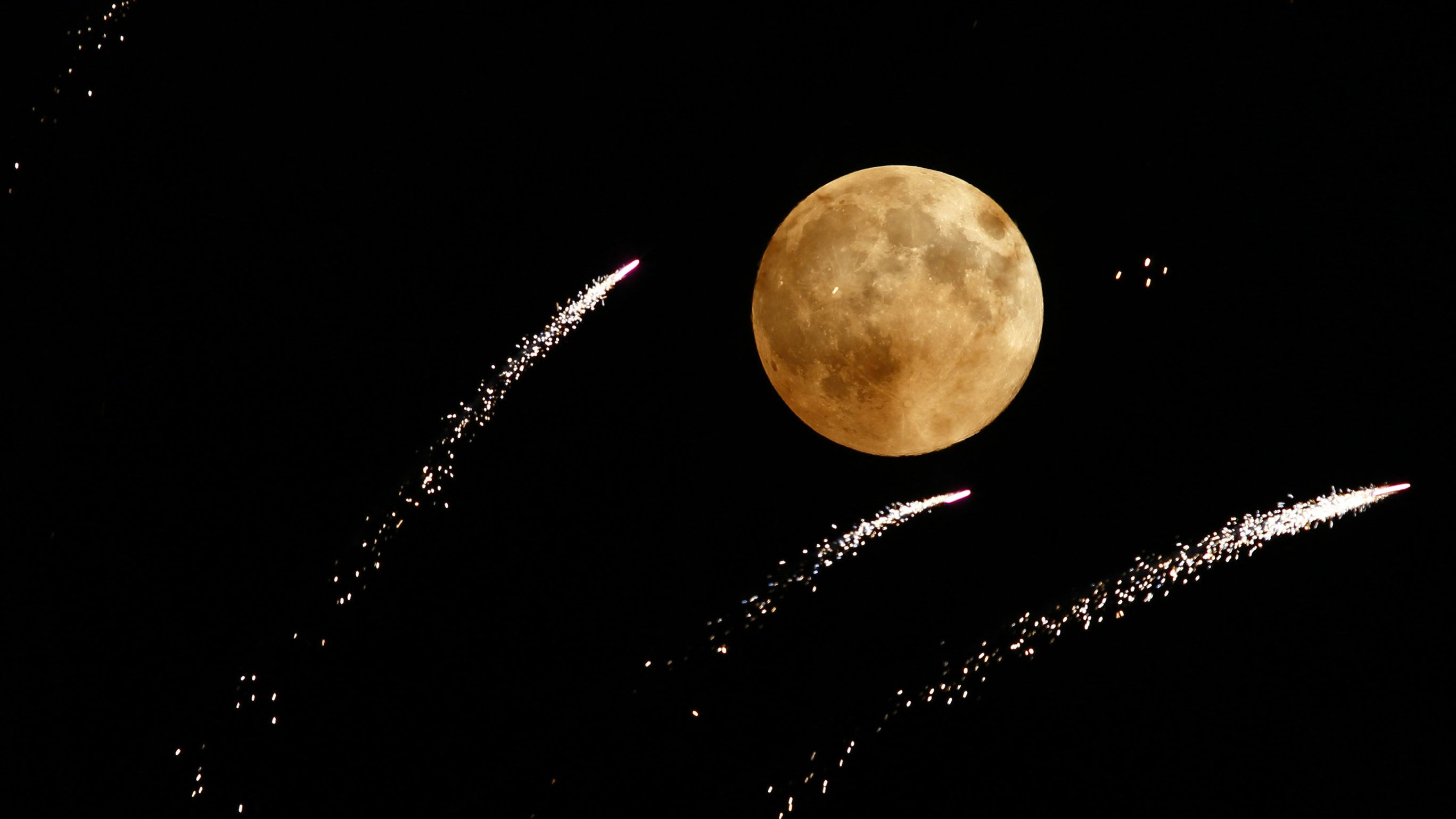 Fireworks streak past in front of the supermoon outside the town of Mosta, celebrating the feast of its patron saint, in central Malta, August 10, 2014. The astronomical event occurs when the moon is closest to the Earth in its orbit, making it appear much larger and brighter than usual.