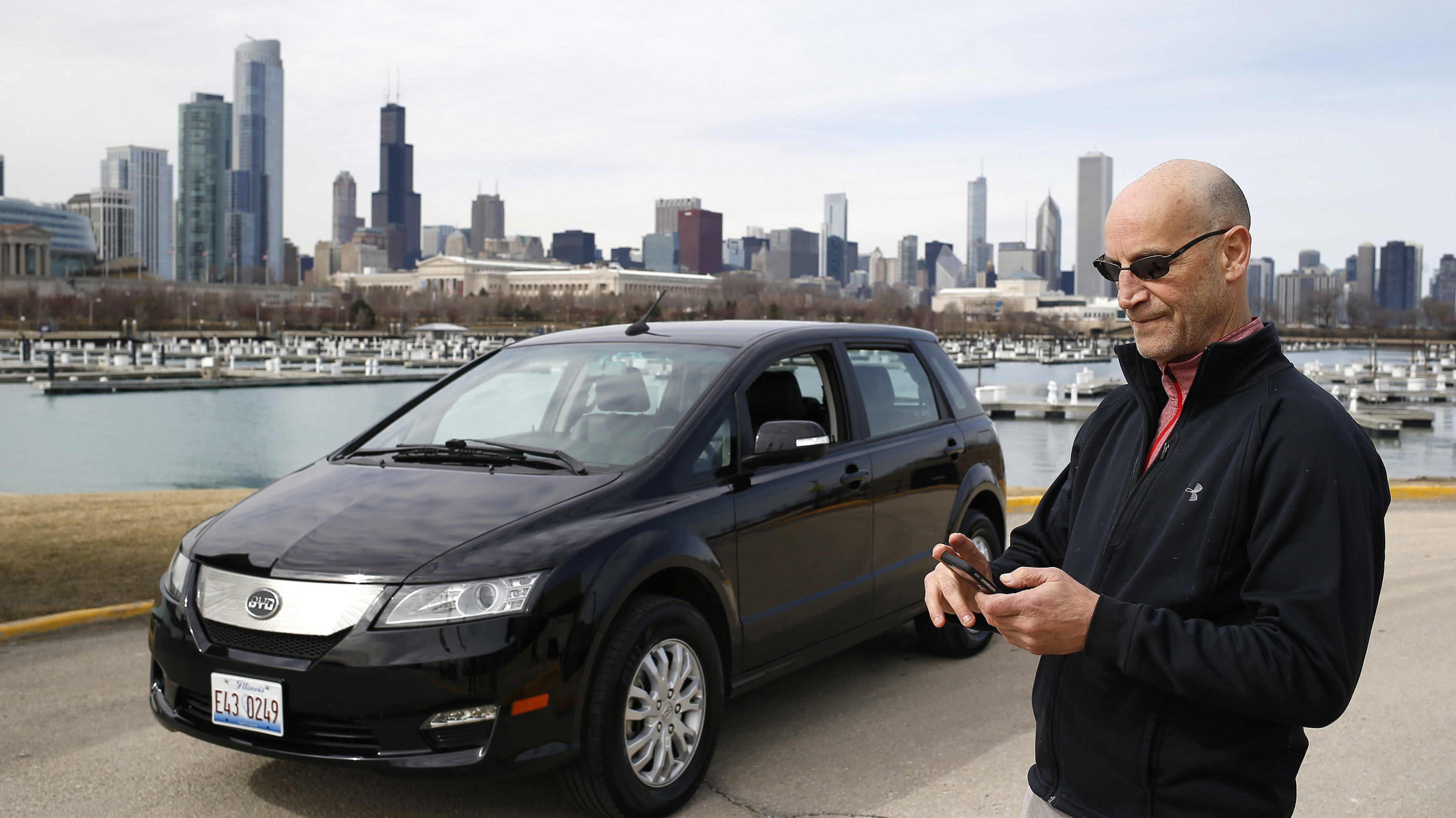 Uber driver Glen Snower looks at his phone next to a BYD e6 electric car in Chicago, Illinois March 18, 2015. Uber, which allows users to summon rides on their smartphones, struck a deal with Chinese automaker BYD Co Ltd to test a fleet of electric cars for its drivers.